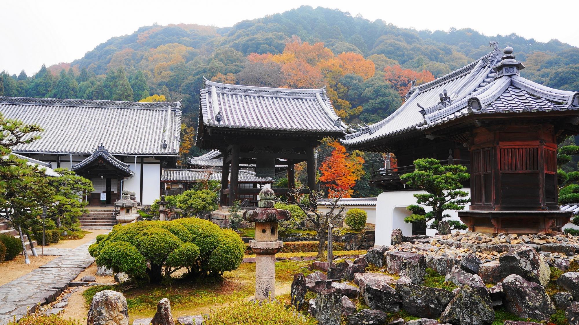 鎮守社や鐘楼の向こうにそびえる秋色に染まる山