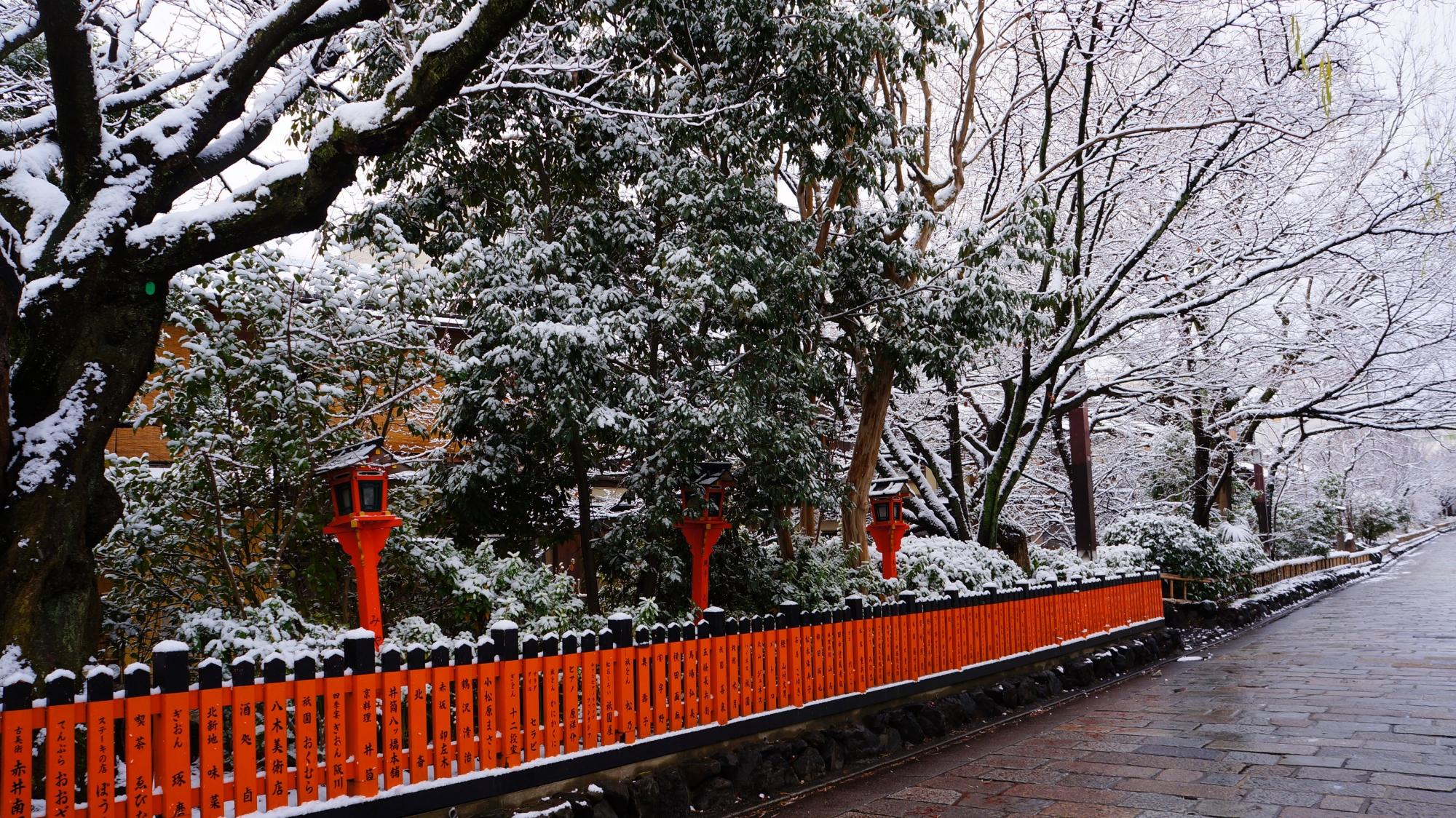 祇園白川の赤い玉垣に映える白い雪