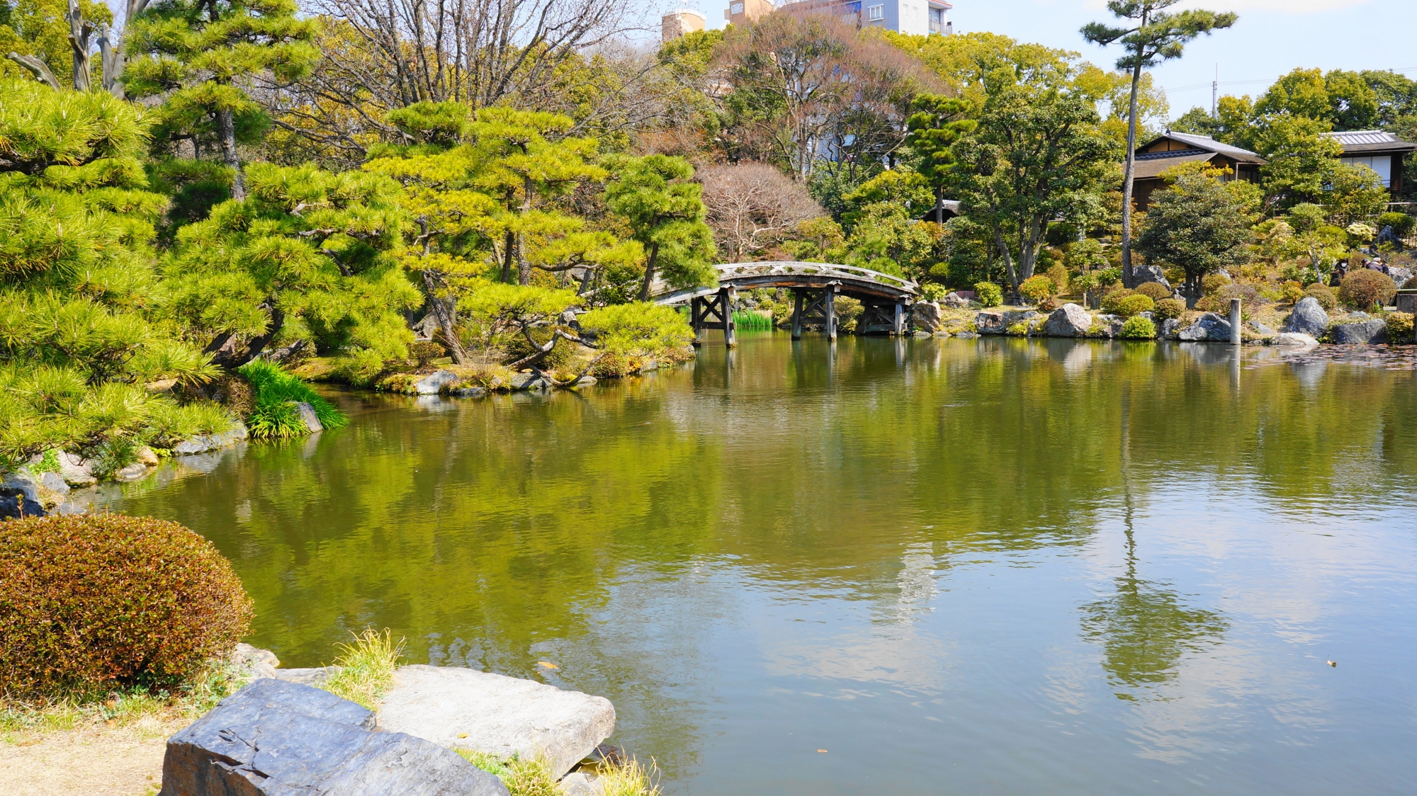自然の溢れる印月池(いんげつち)とそこに架かる侵雪橋(しんせつきょう)と真ん中に浮かぶ北大島(きたおおしま)