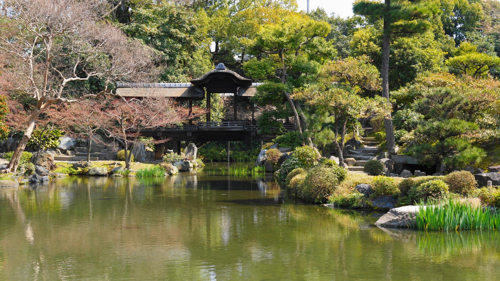 緑あふれる庭園と池の中に佇む回棹廊