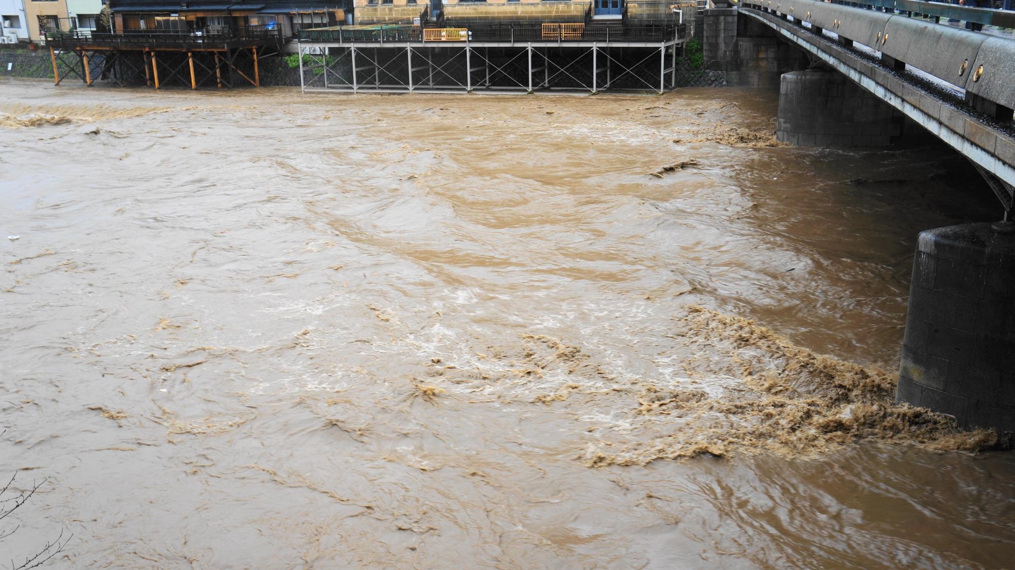 四条大橋の橋桁にあたり茶色い水しぶきが上がる鴨川