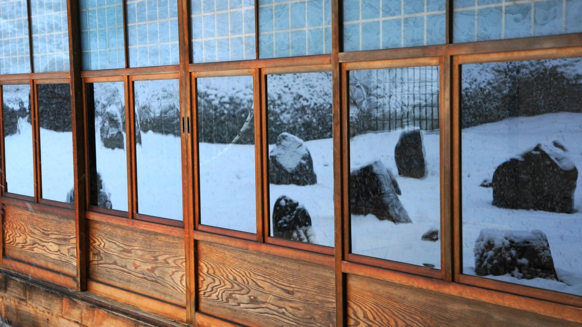 光明院の書院のガラス戸に映る庭園の雪景色