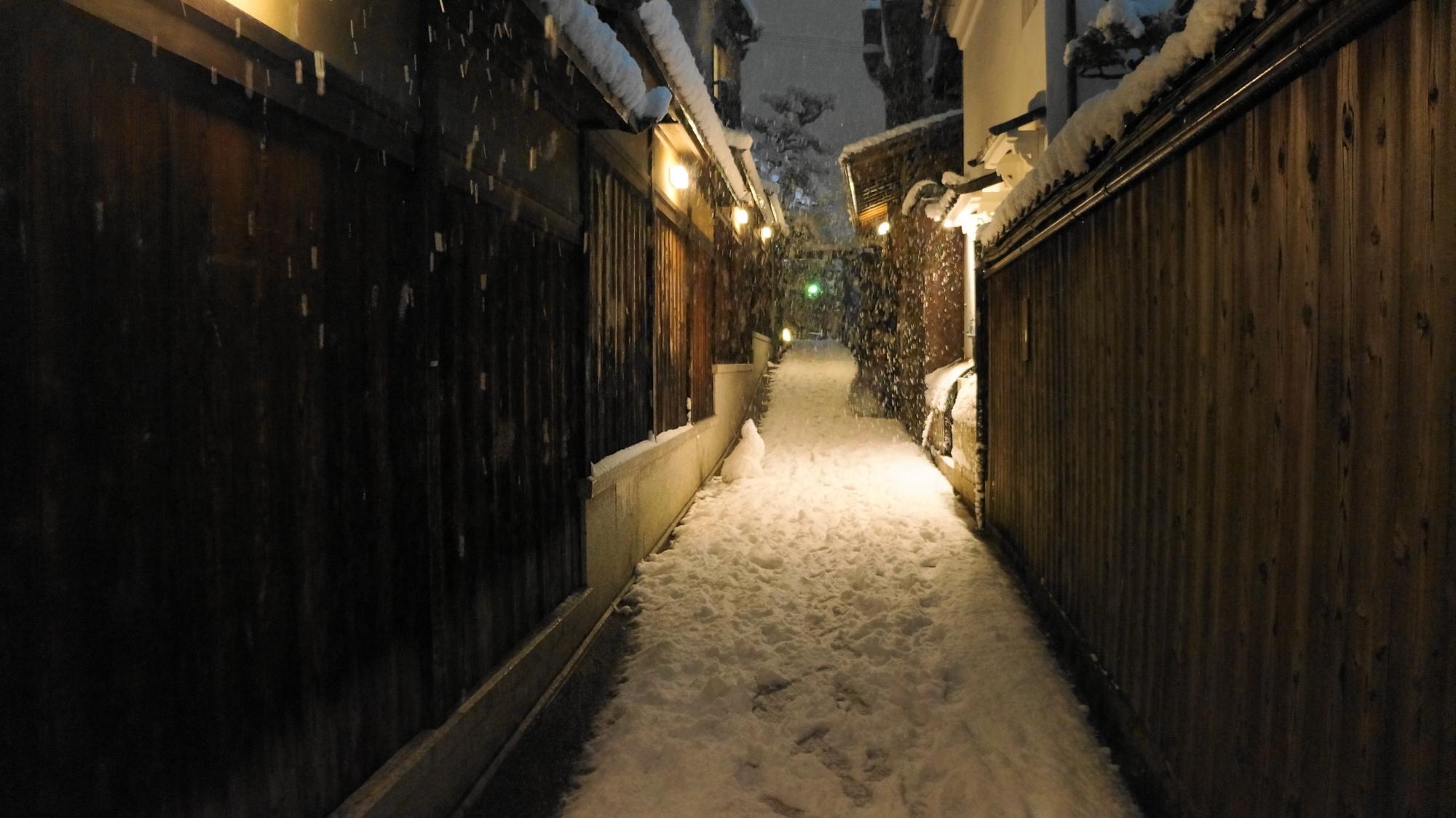 木の塀に囲まれた雪の細い道