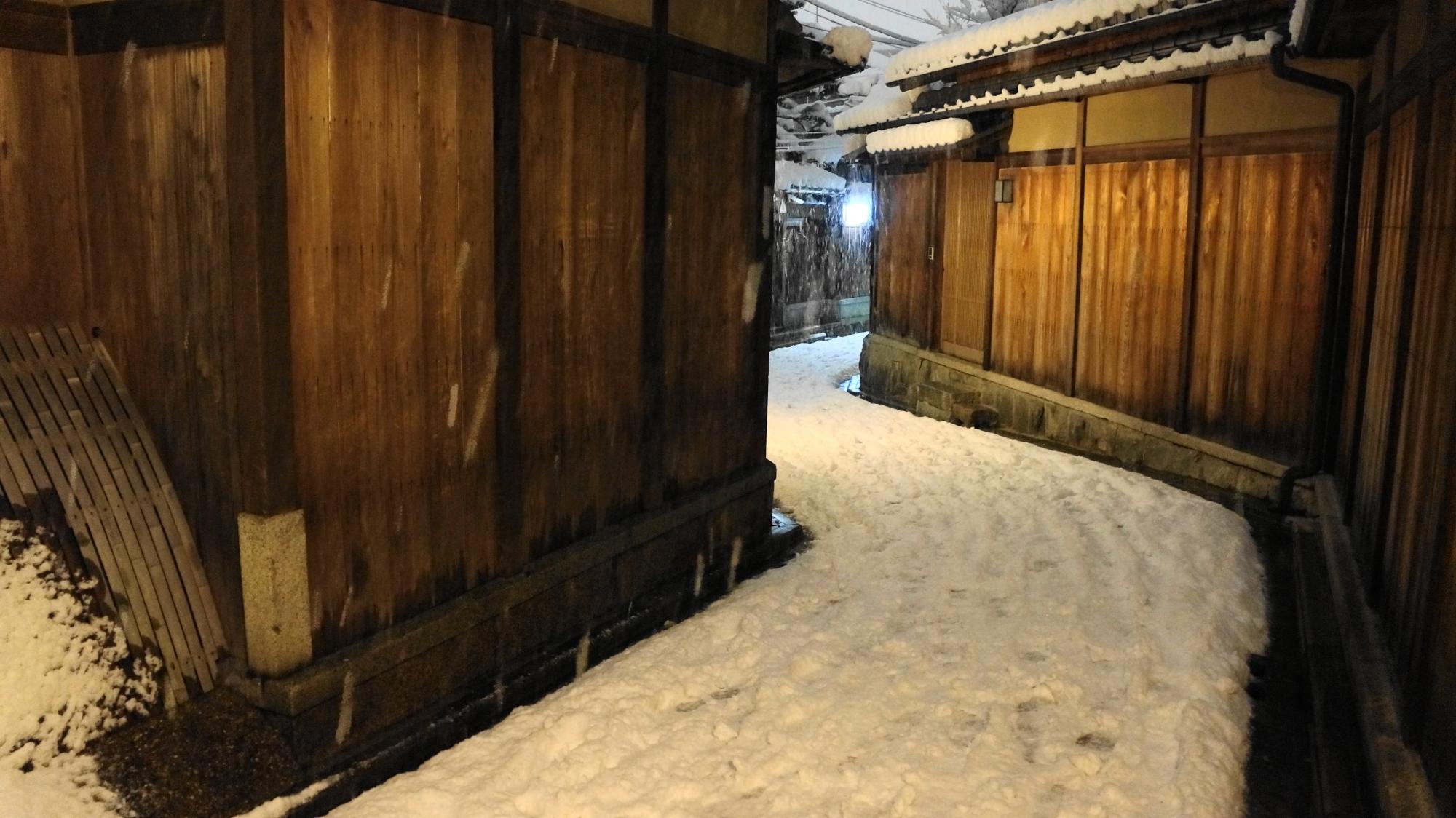 曲がりくねった石塀小路の雪景色