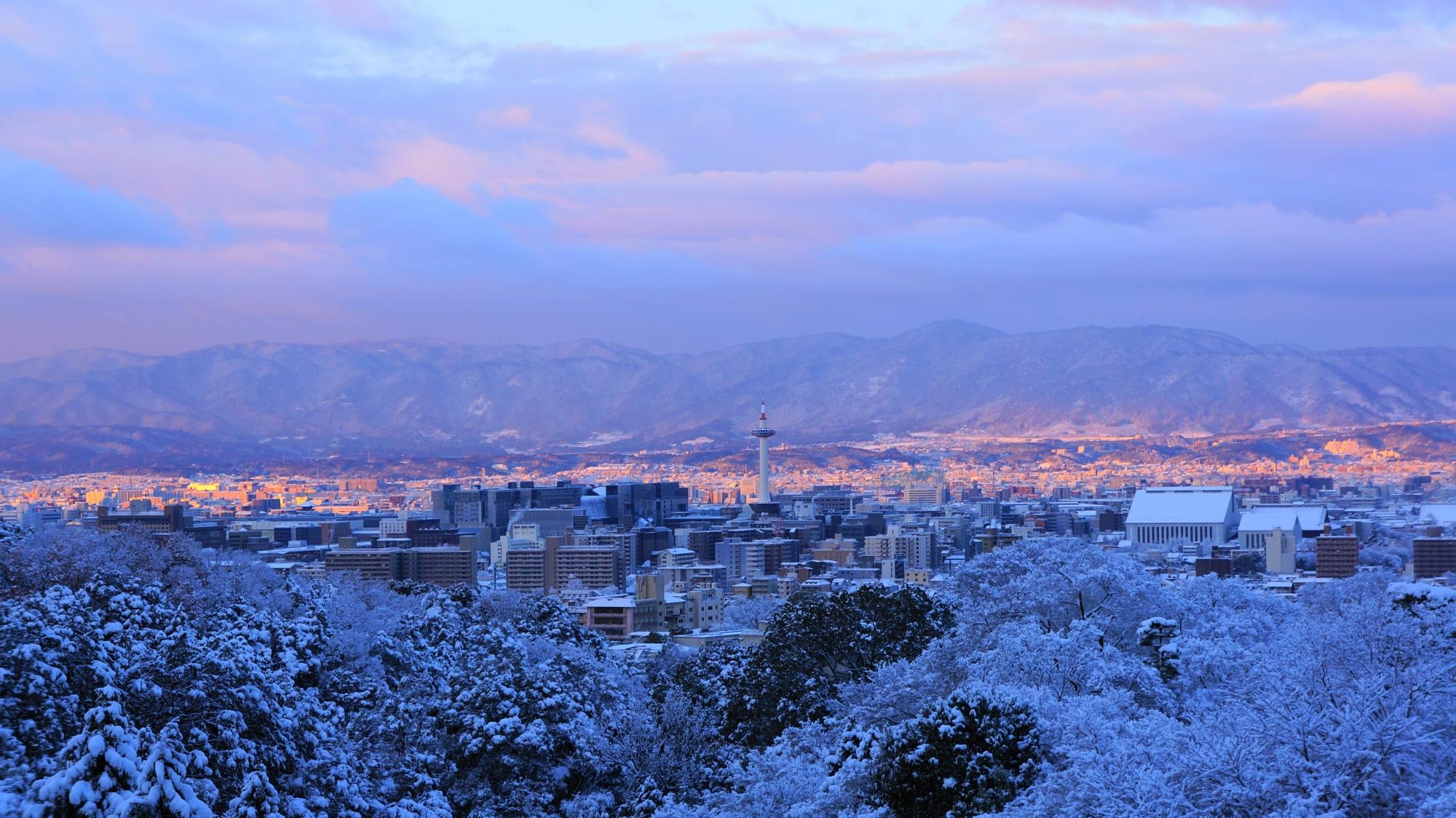 朝焼けと朝日がピンクに照らす雪の京都市街と京都タワー