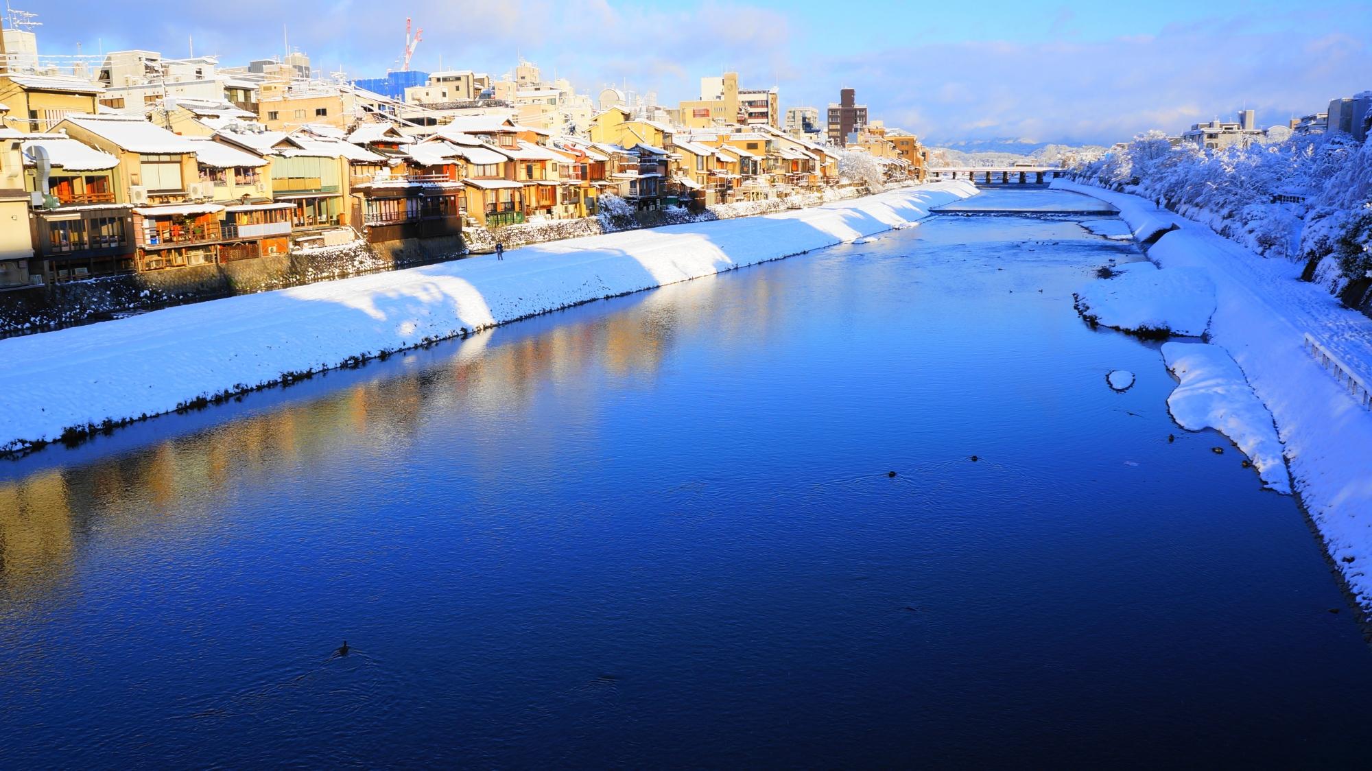 青く輝く雪の鴨川の水面と水鏡