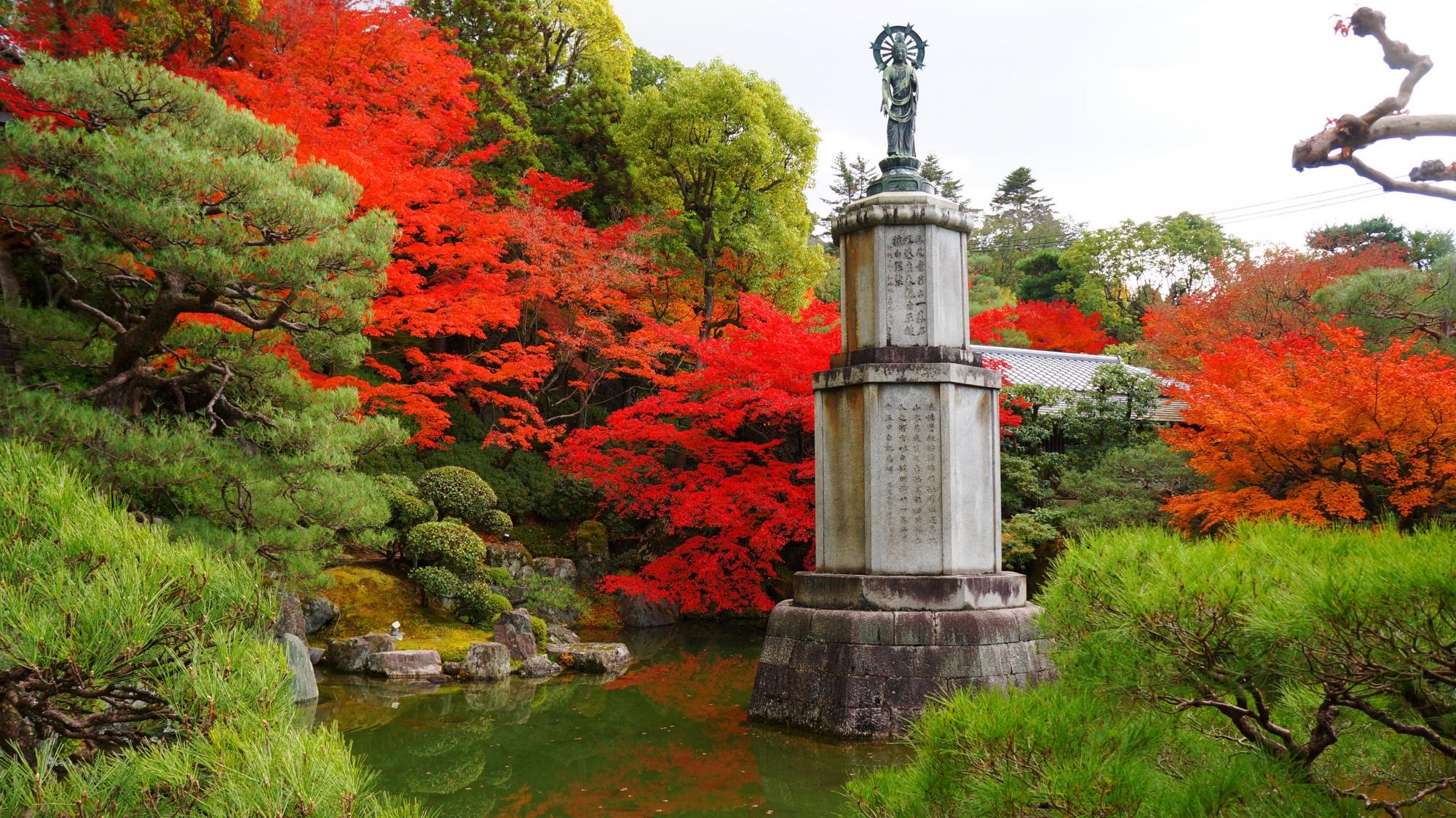 松などの多様な緑と水辺を彩る赤やオレンジの多彩な紅葉