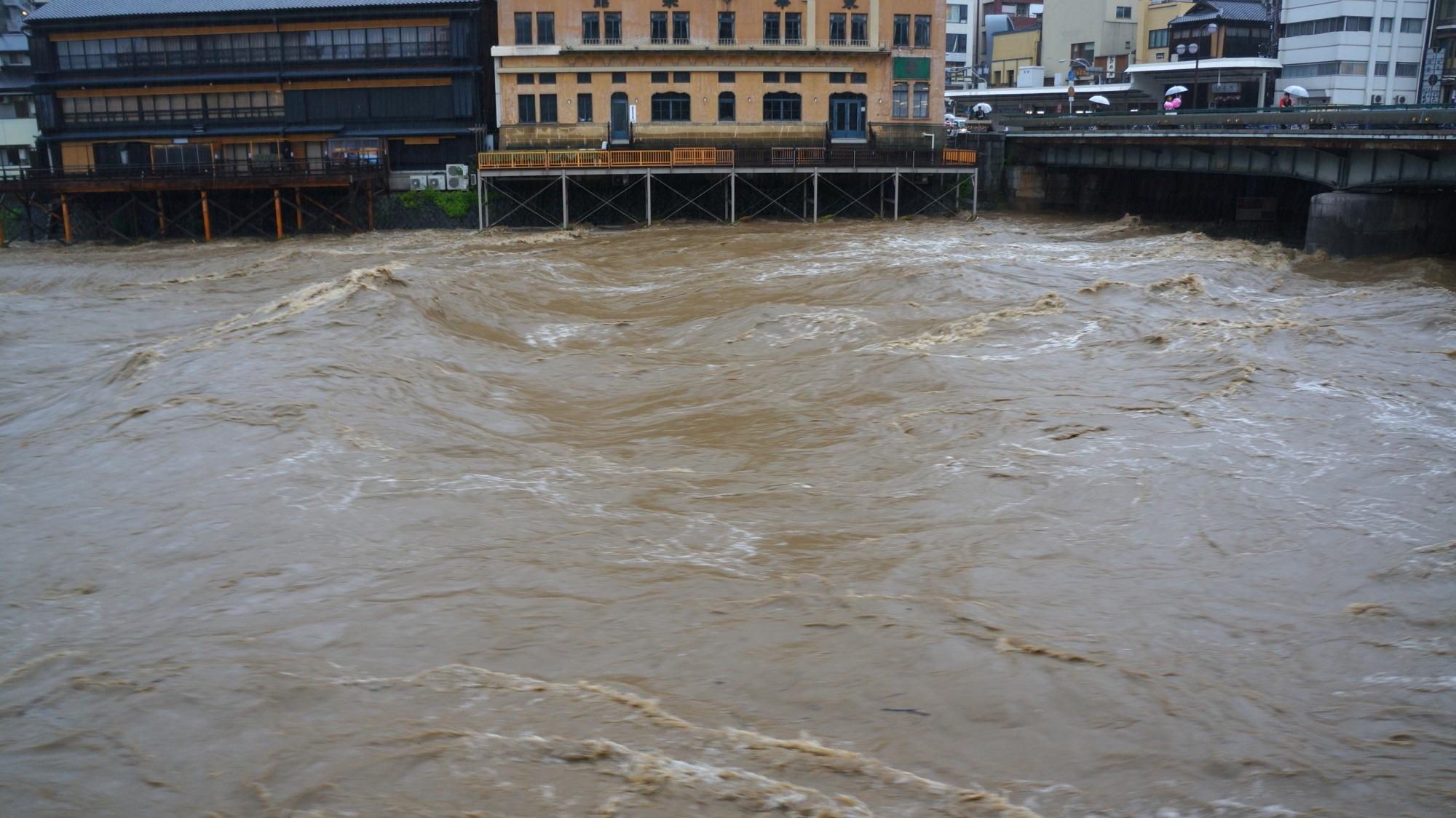 四条大橋も川床も大量の水に飲み込まれそうな増水した鴨川
