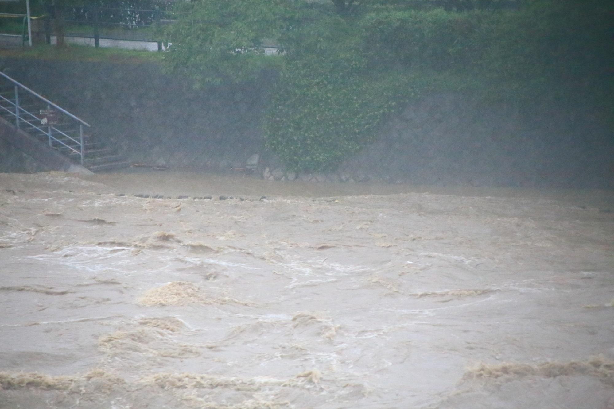 階段から降りたところには茶色い水が迫っている鴨川