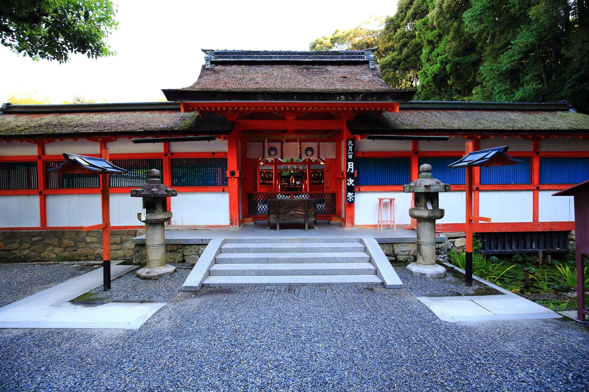白壁に朱色の上品な門と珍しい青色の格子の吉田神社の本宮