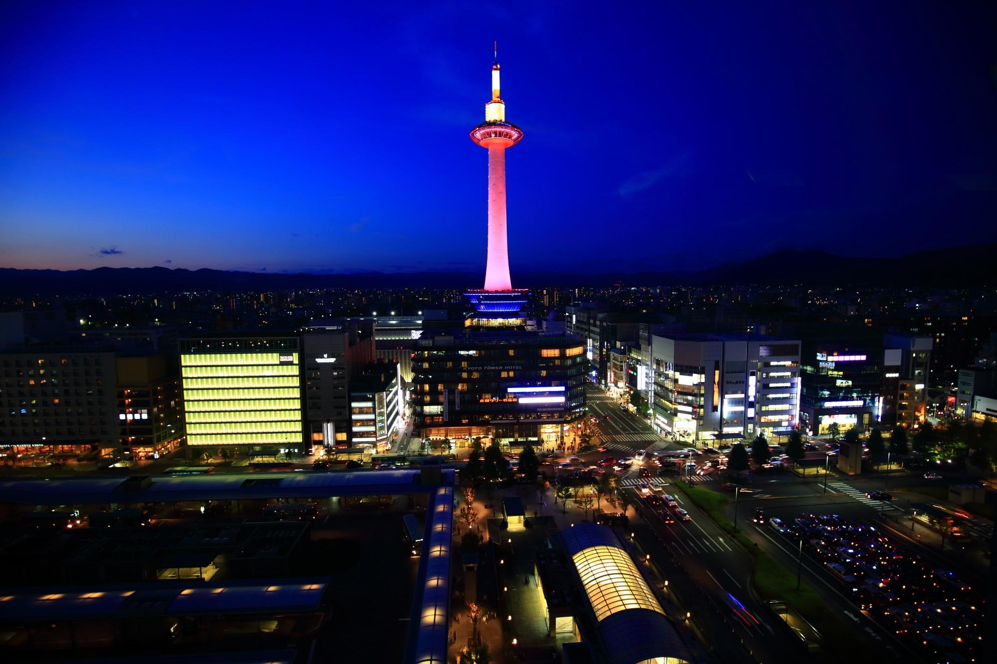 ピンクリボンライトアップの京都タワー(駅ビル空中経路)と夜景と葵色の空