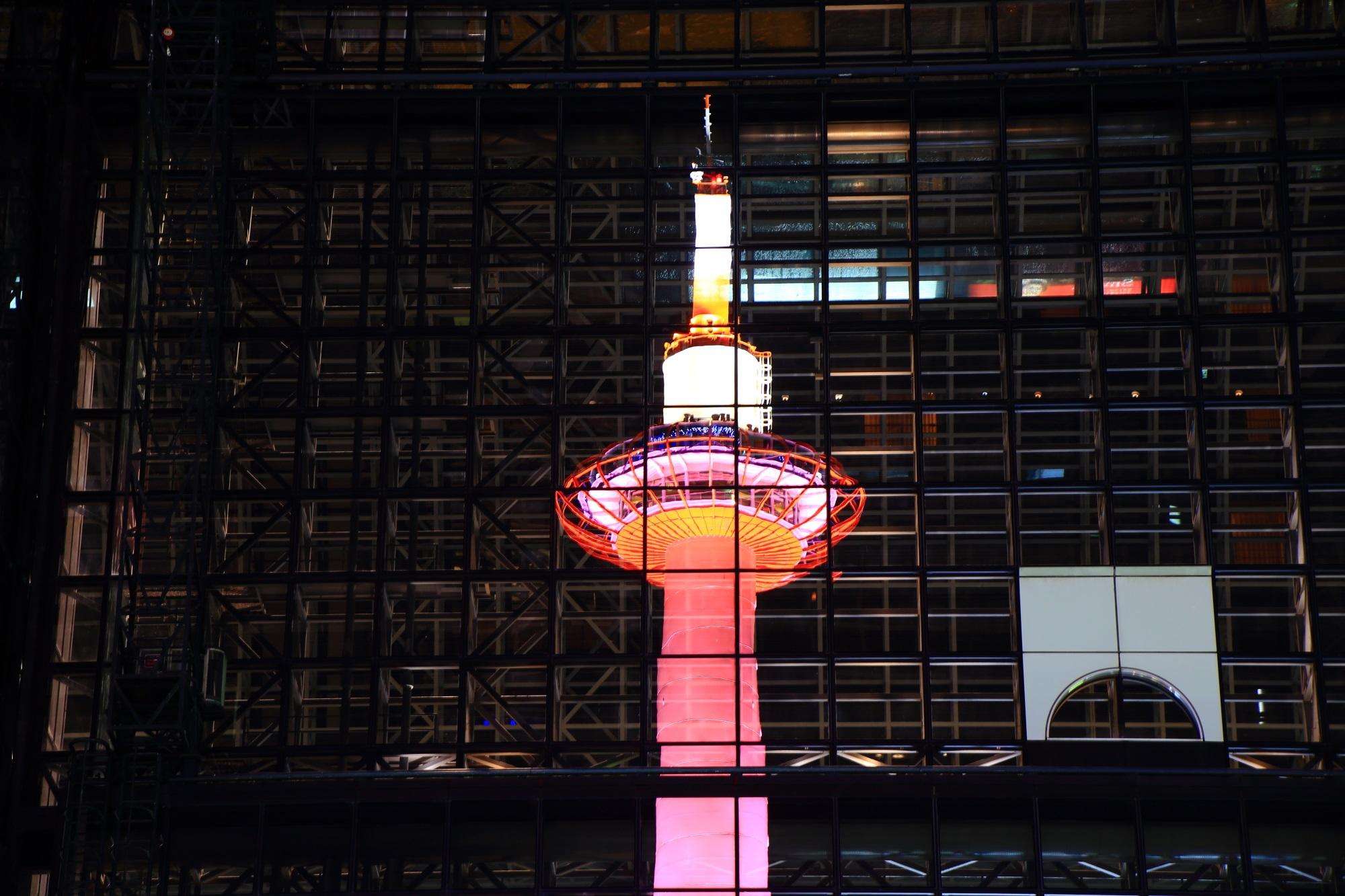 京都駅ビルに映るピンクリボンライトアップの京都タワー