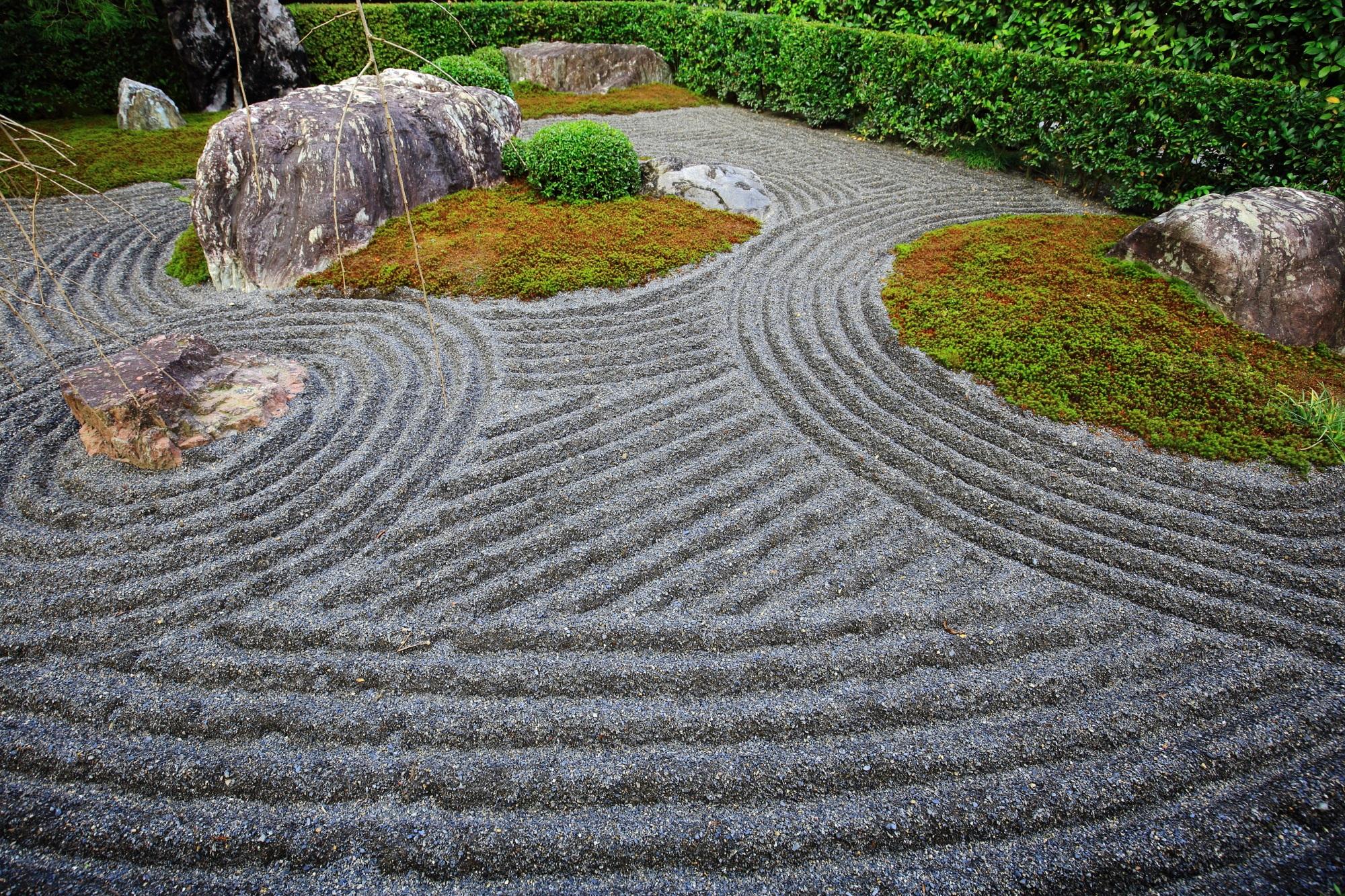 しっかりと波模様の入った砂に苔と岩が浮かぶ陰陽の庭