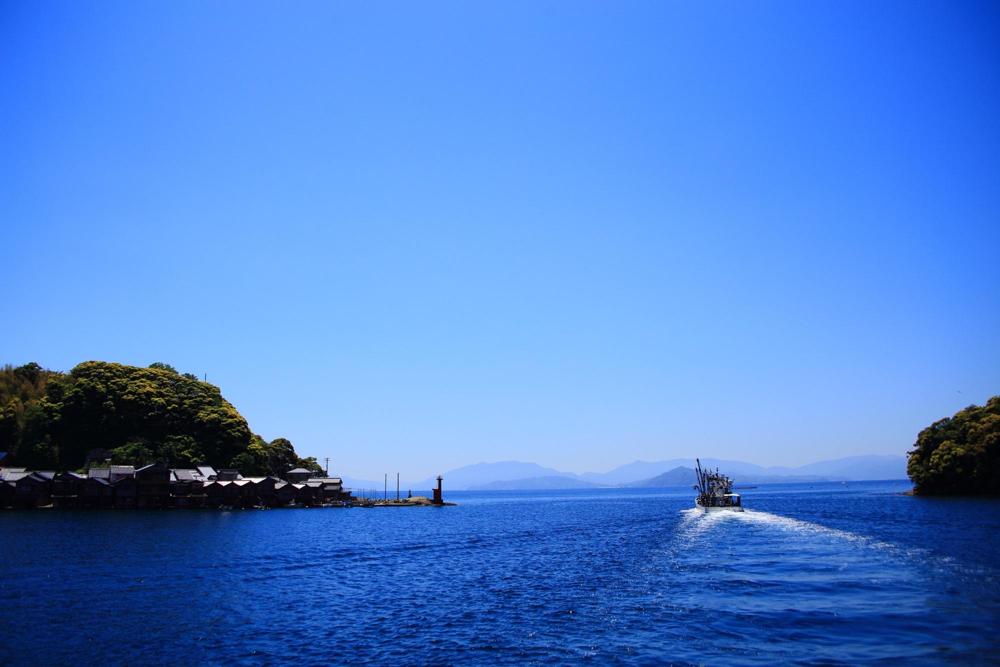 伊根湾から大きな海へ出航していく漁船