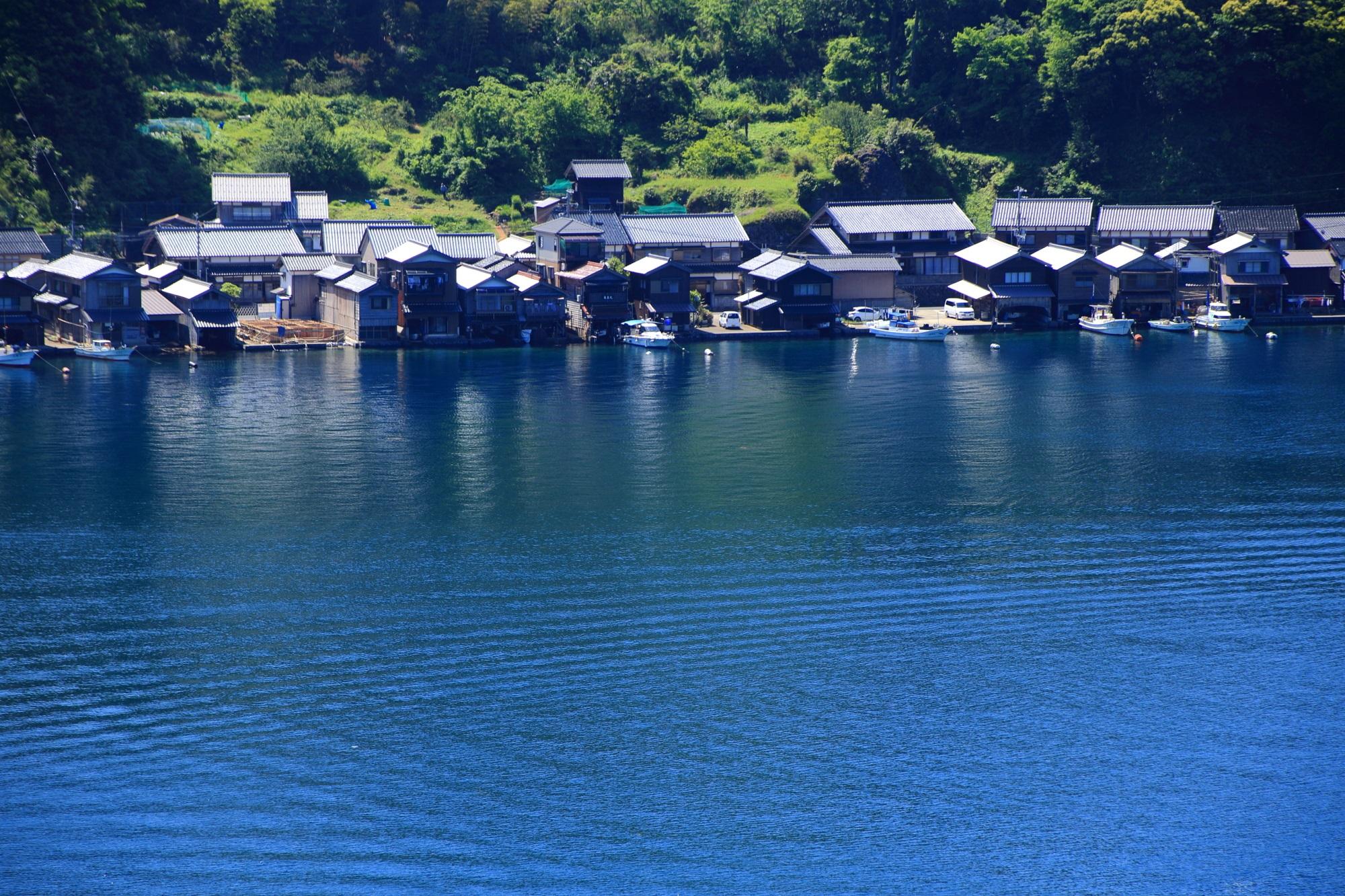 穏やかな海と緑につつまれる独特の舟屋の情景