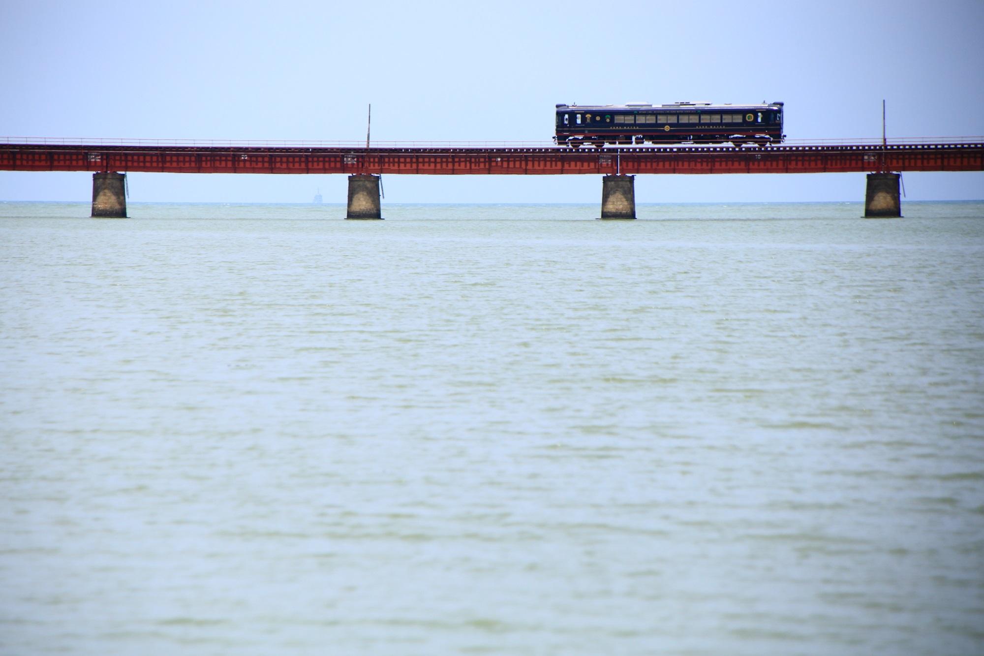 海を走る丹後鉄道のくろまつ号と由良川橋梁