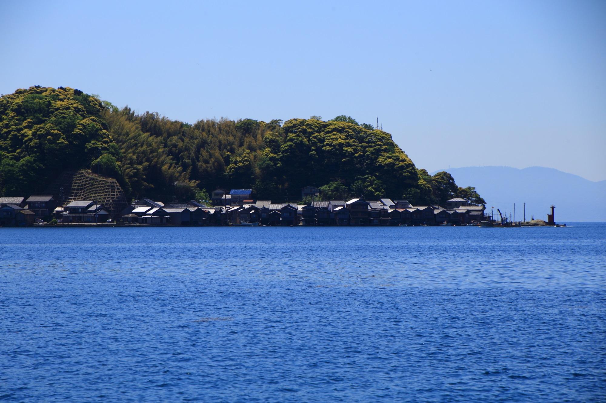 山を背景にして海面に建ち並ぶ伊根の舟屋