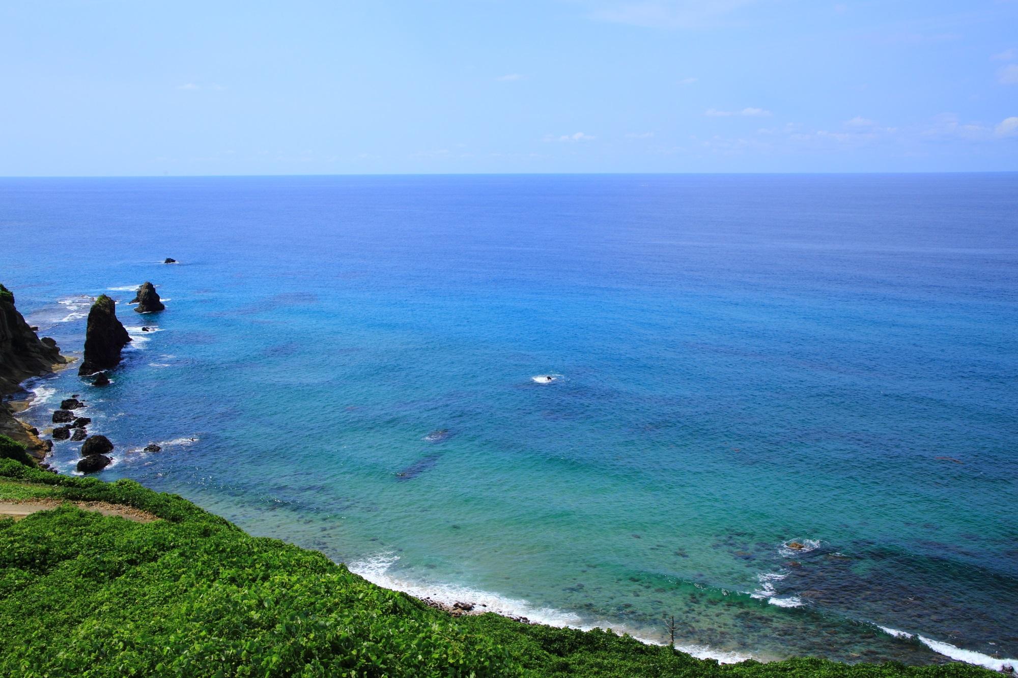 青と緑の透き通った凄い色の海と屏風岩