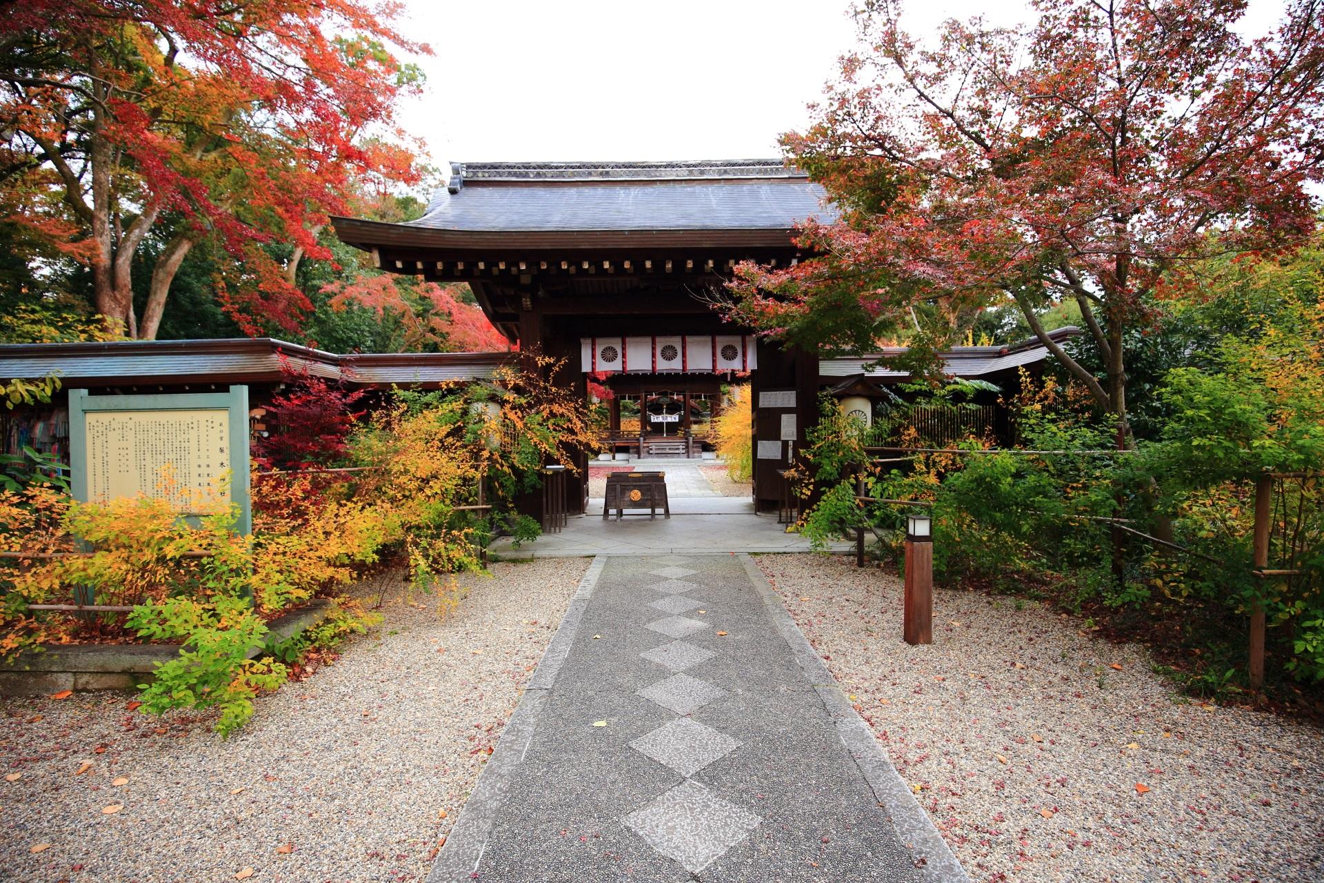 奥に拝殿や本殿がある梨木神社の神門と紅葉