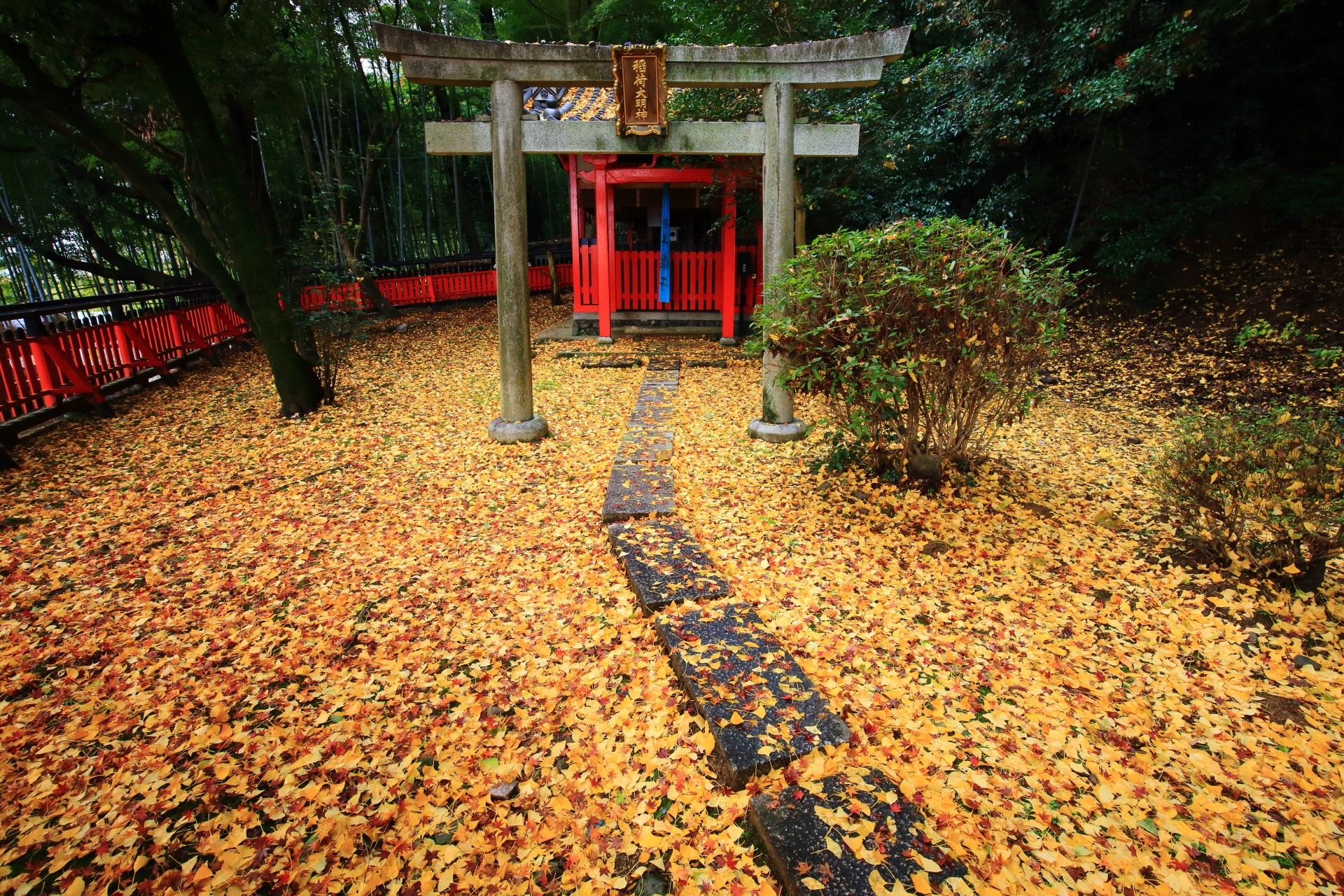 黄色い敷き銀杏の奥にある稲荷社の本殿