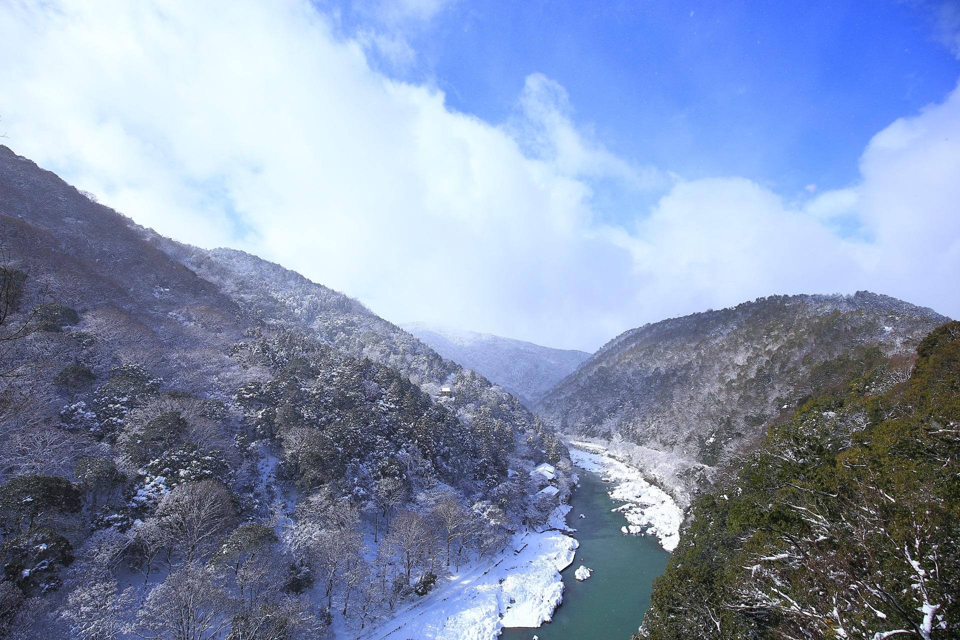 雪の落ちだした嵐山と保津峡と青空