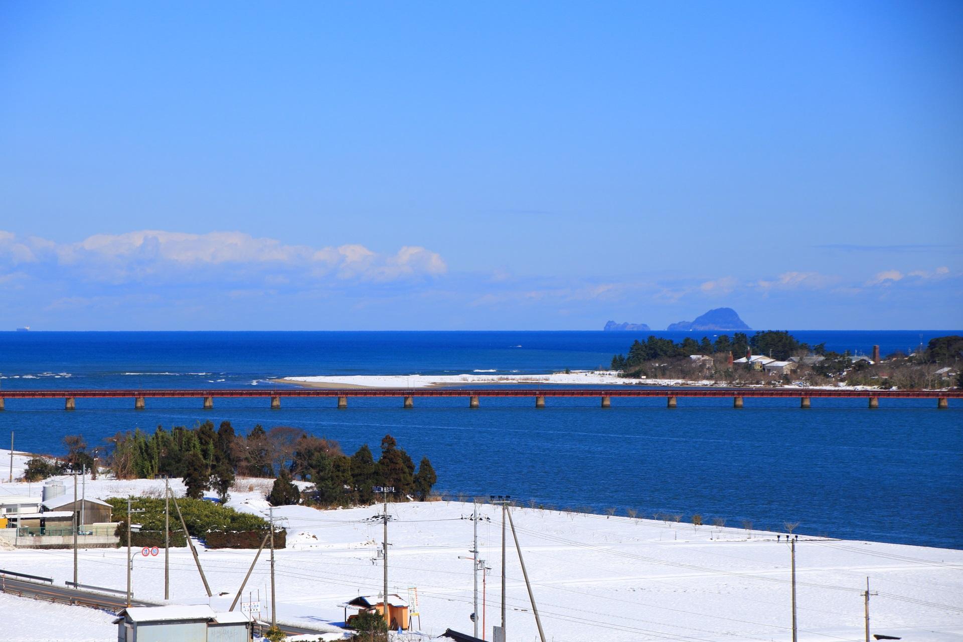 雪の由良川橋梁と青空と青い海
