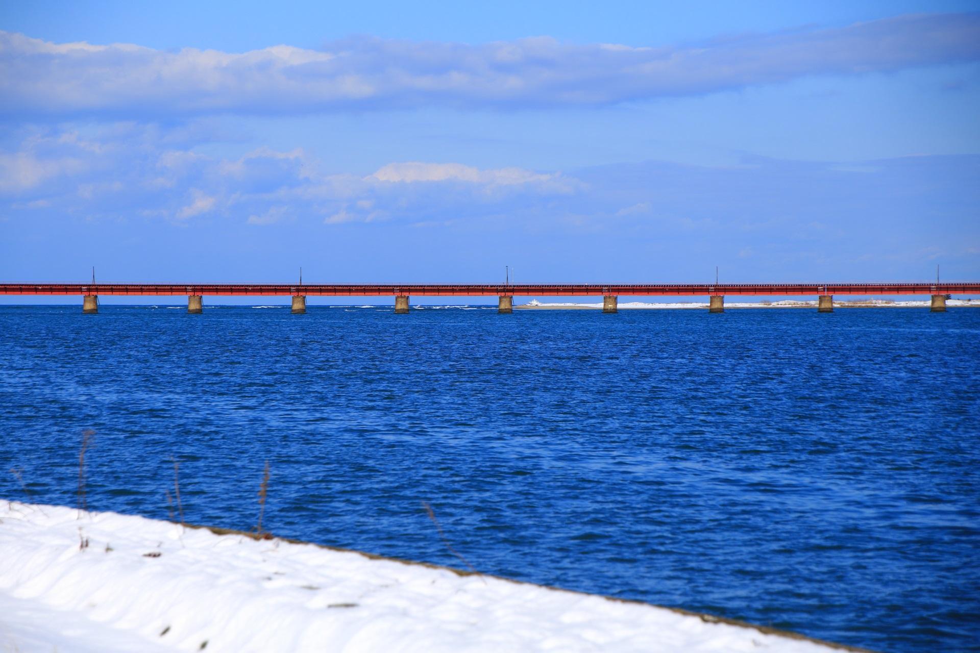 海の上を走る由良川の鉄橋と青空