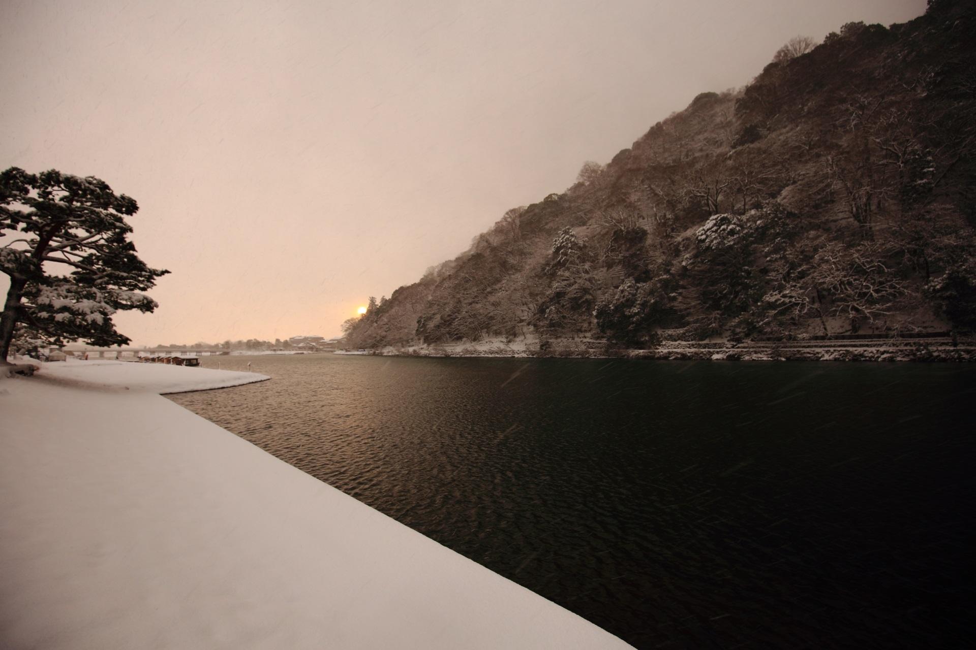 桂川と嵐山の夜明けの雪景色