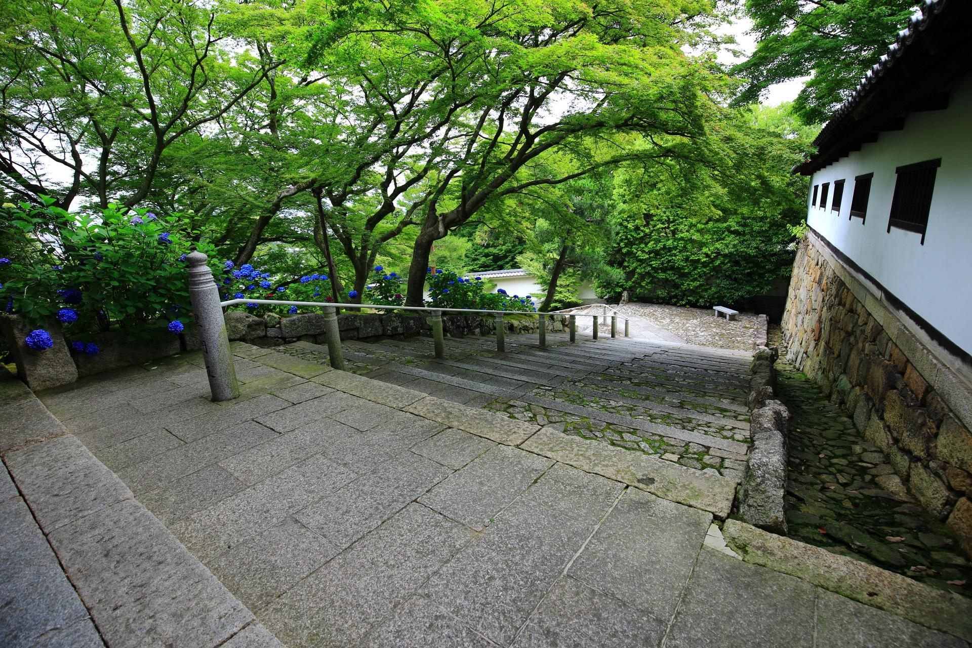 石と白壁と緑につつまれた風情ある空間の黒門坂
