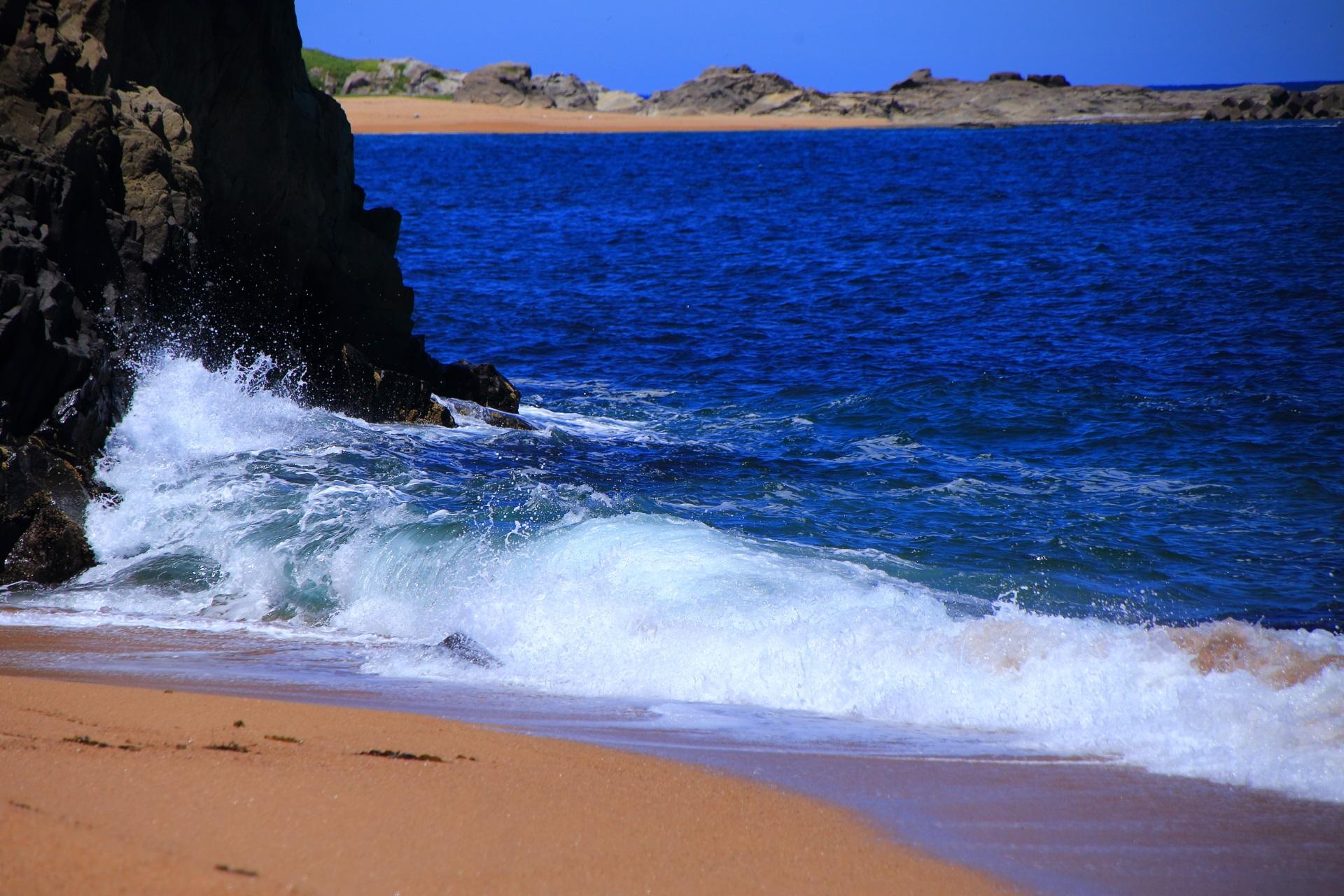 砂浜を潤し岩を削る京丹後の間人の海の波