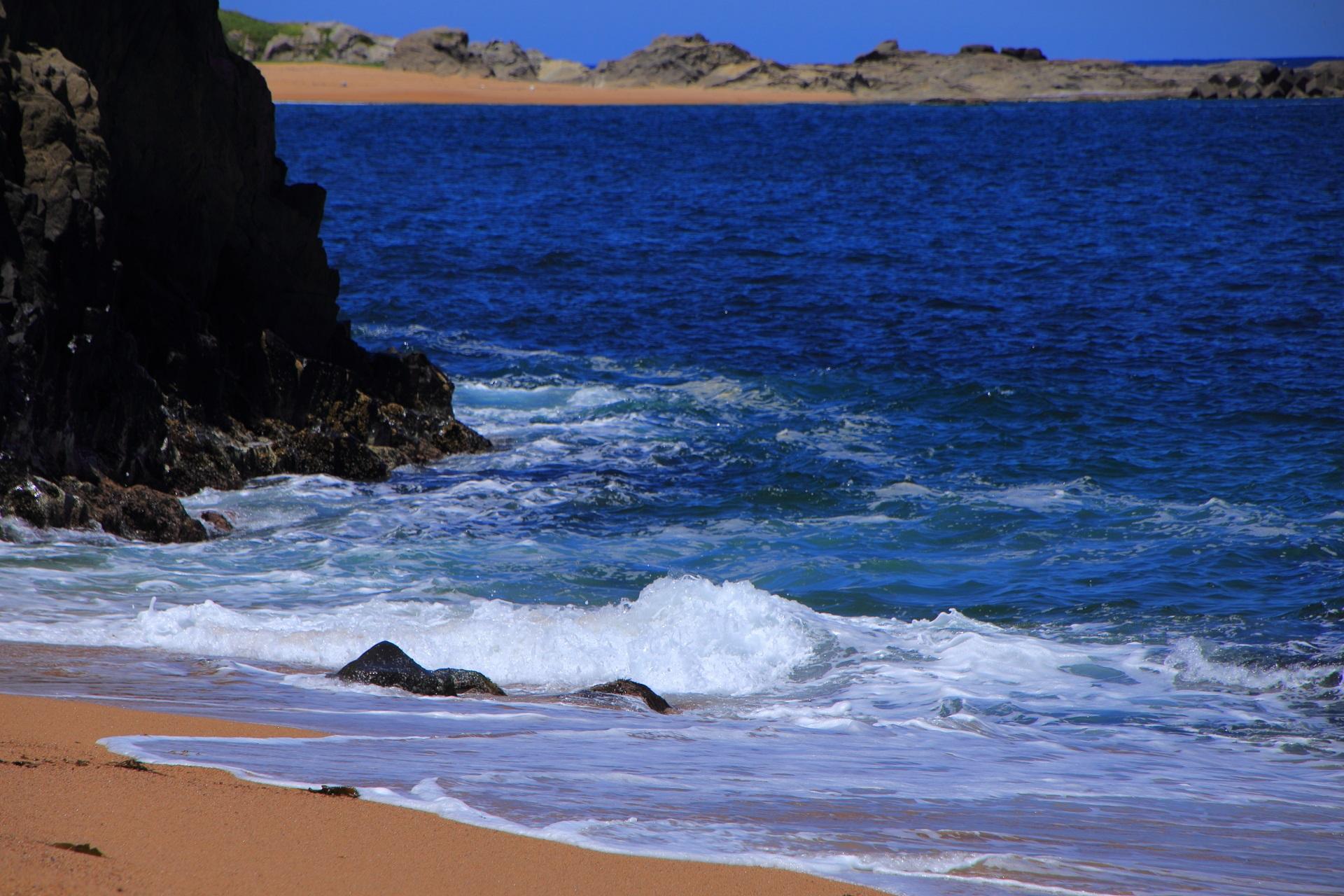 眩しい海岸に打ち寄せる波や水しぶきが眩しく美しい京丹後の間人(たいざ)