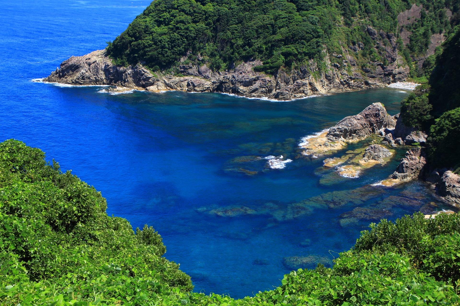 カマヤ海岸の緑と岩に囲まれた美しい青い空間