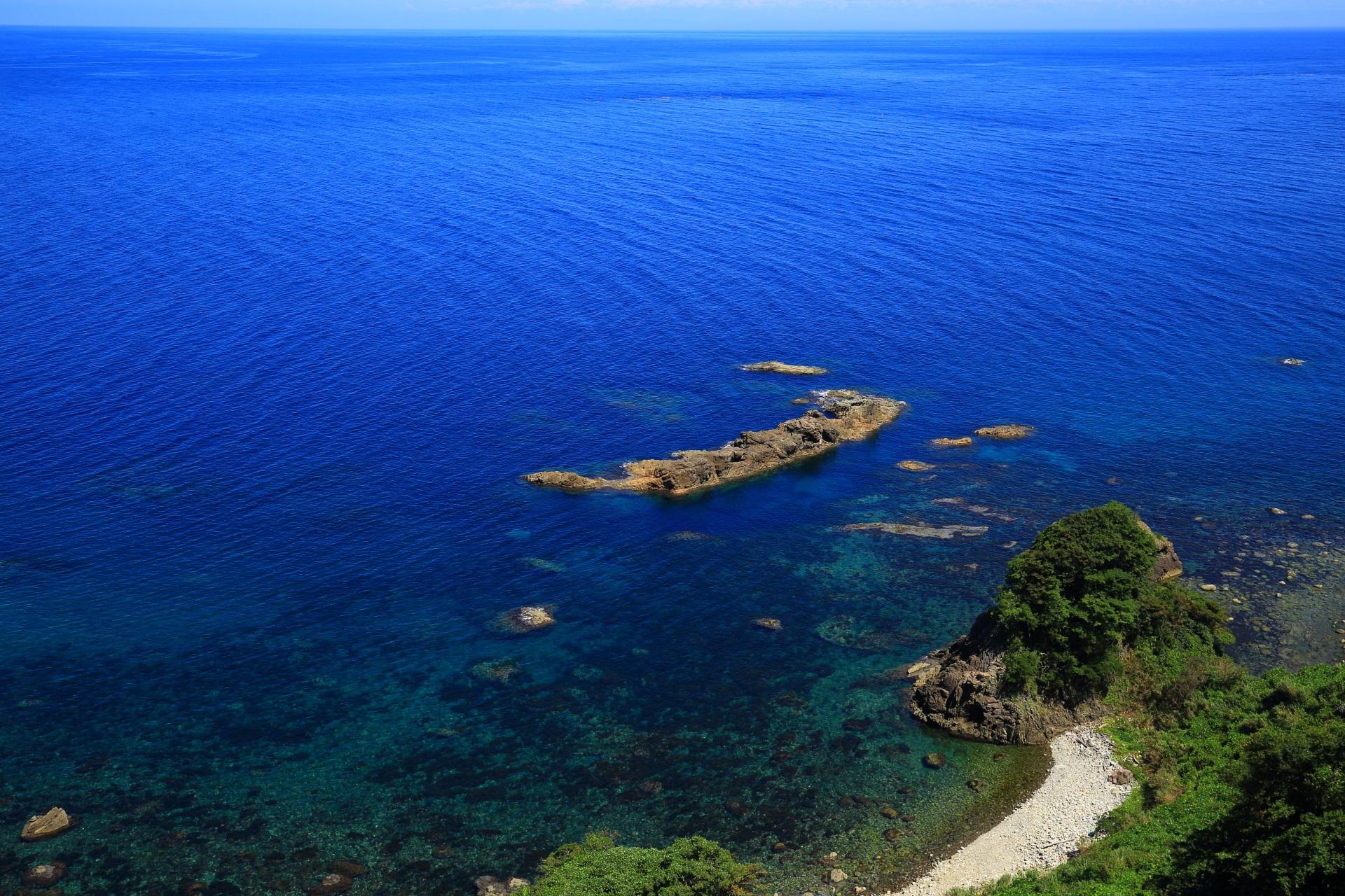 カマヤ海岸の青い海と一文字の岩とアクセントになる白い砂浜