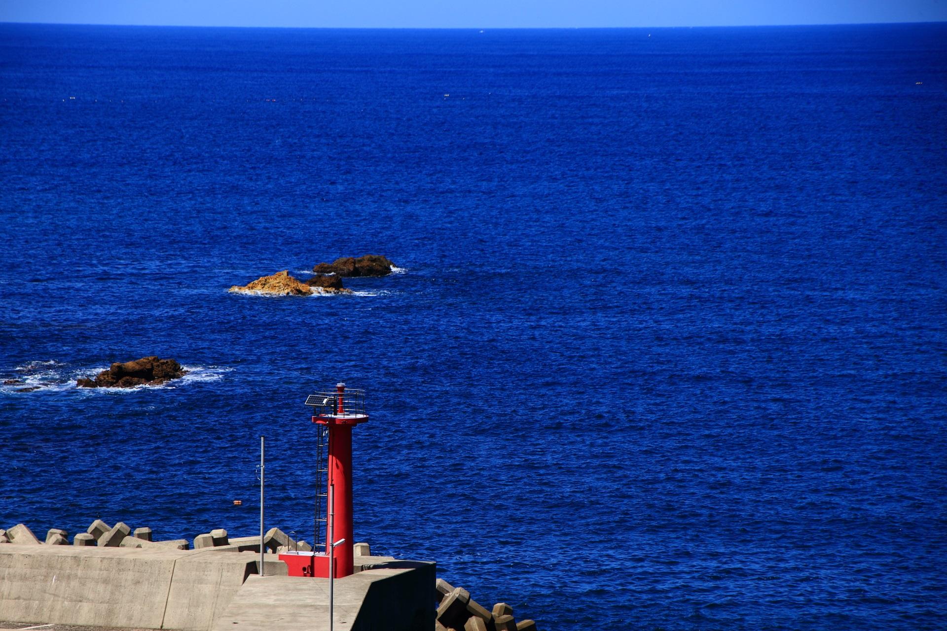五色浜の西側にある川の河口付近の赤い灯台と青い日本海