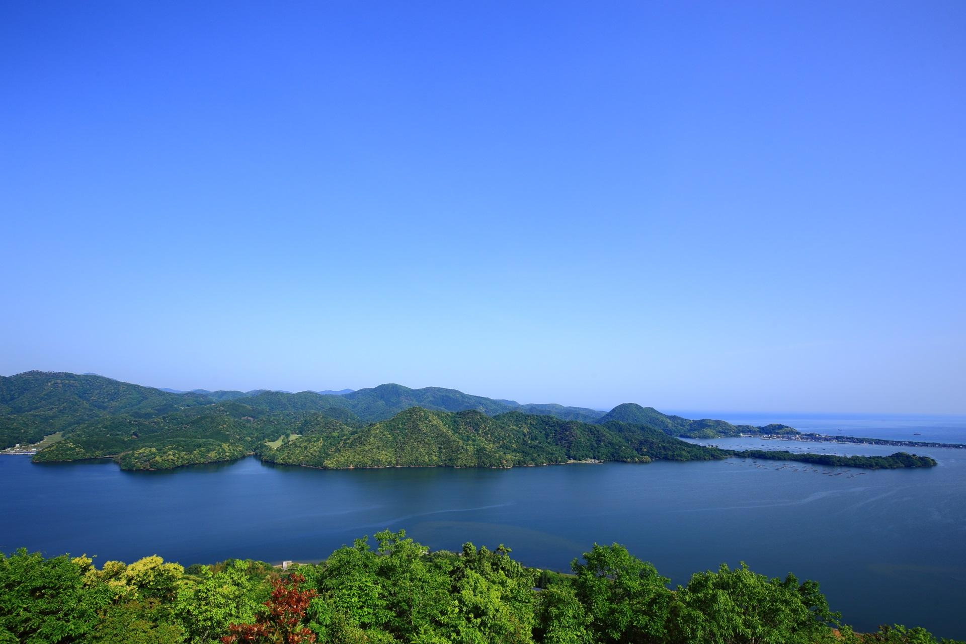 穏やかな湖と海と連なる滑らかな山々の絶景