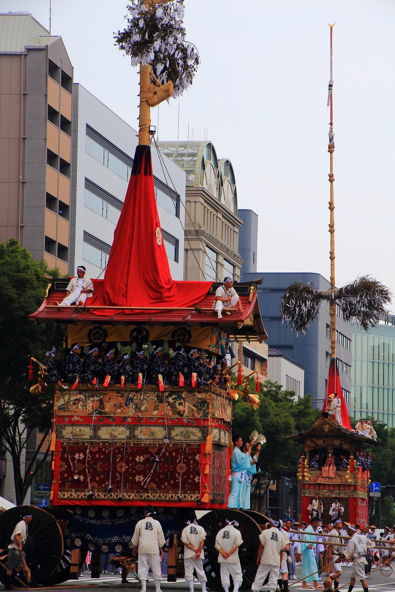 ビルの高さ位ある巨大な鶏鉾と月鉾の日常と非日常の融合した景色