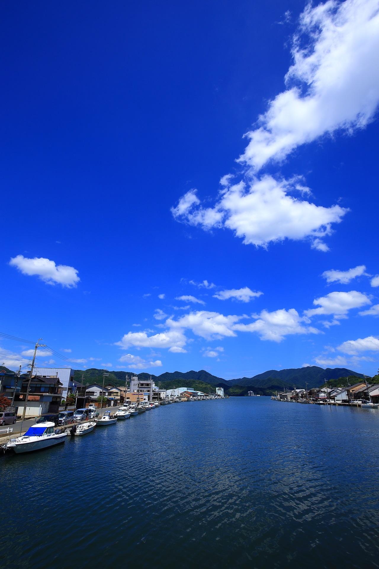青空と白い雲の下の漁船が似合う綺麗な伊佐津川