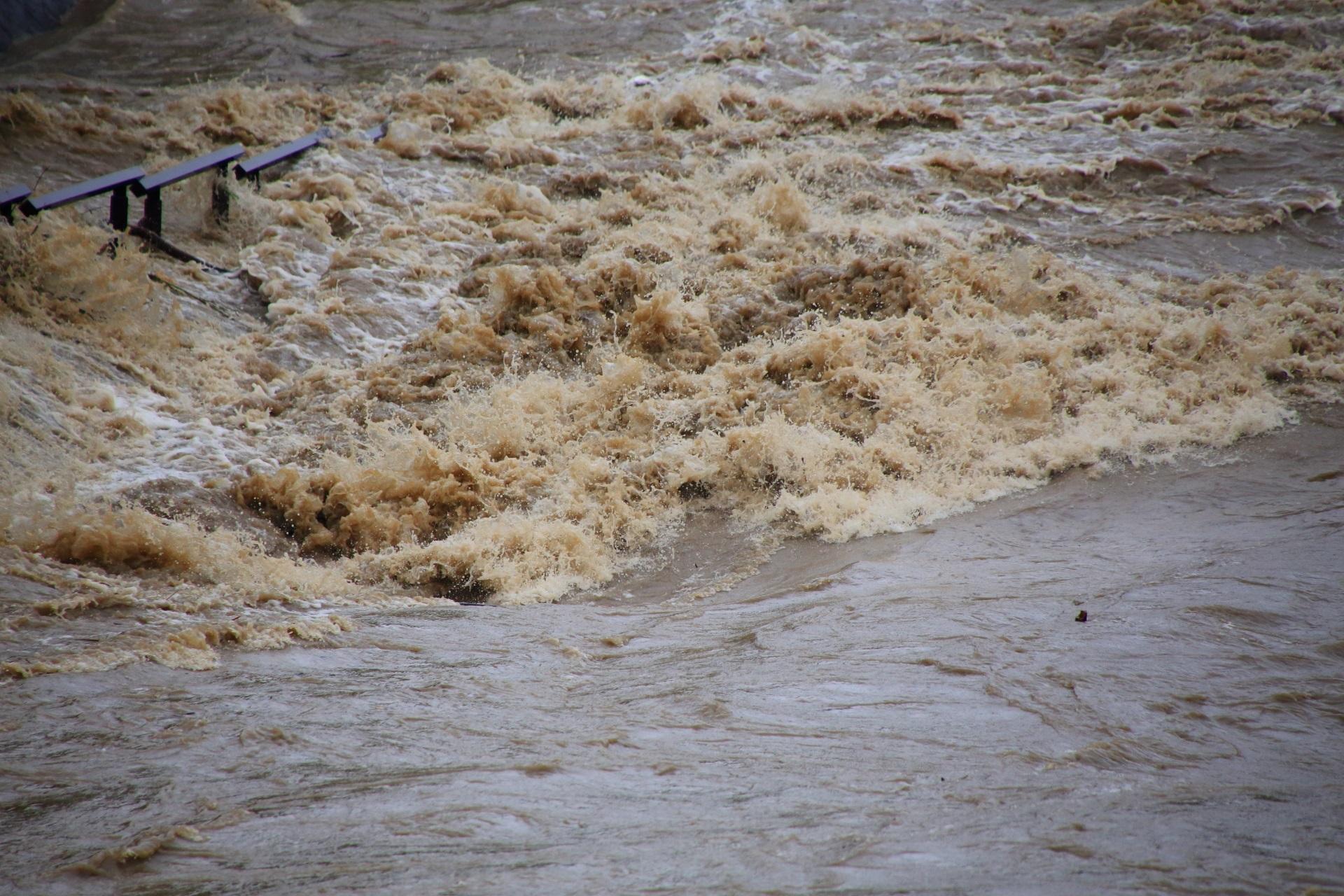 鴨川の激流がぶつかってあがる茶色い水しぶき