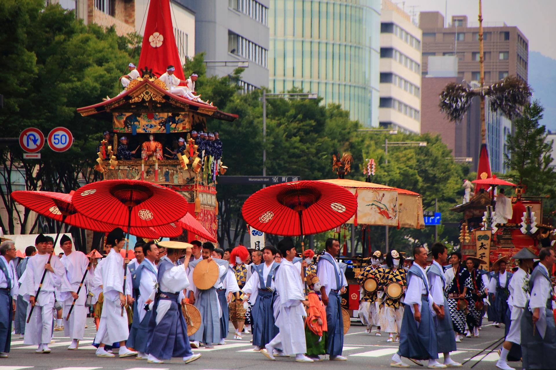 大きな傘や棒振り囃子らで構成される傘鉾の綾傘鉾と後ろの大きな月鉾