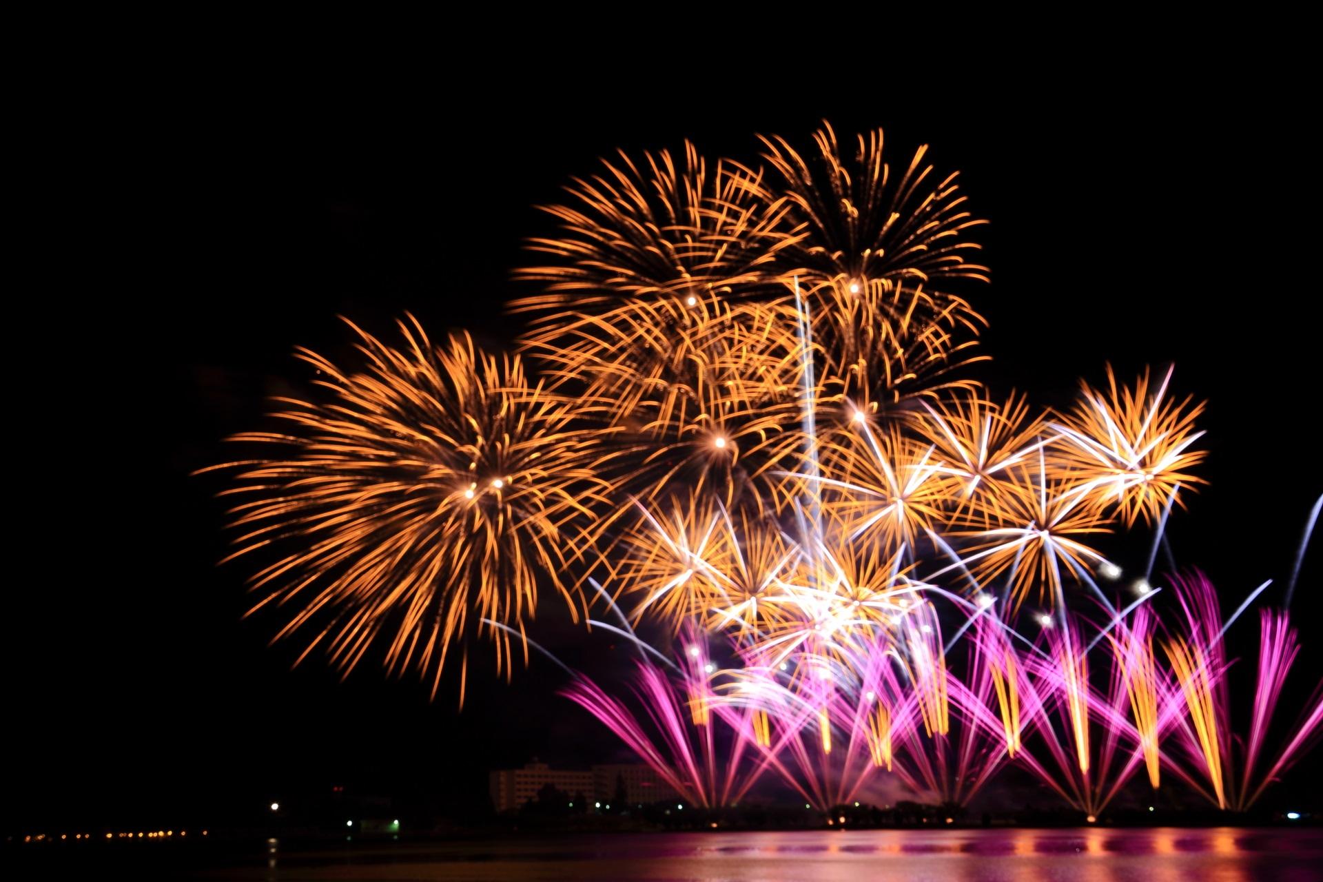 舞鶴港をそめる上はオレンジで下は紫の花火