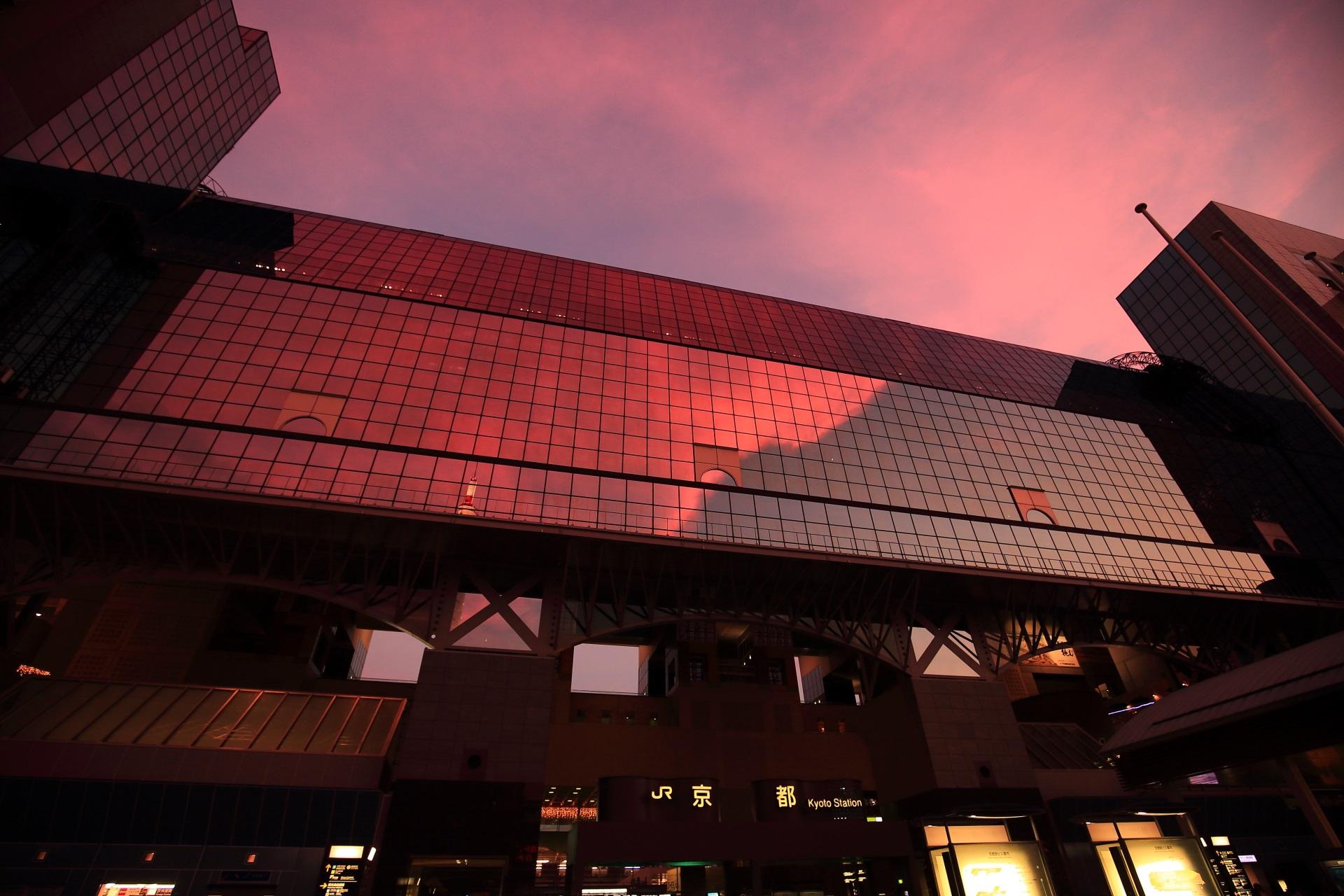 艶やかな色合いの雲と空が映る駅ビル正面のガラス