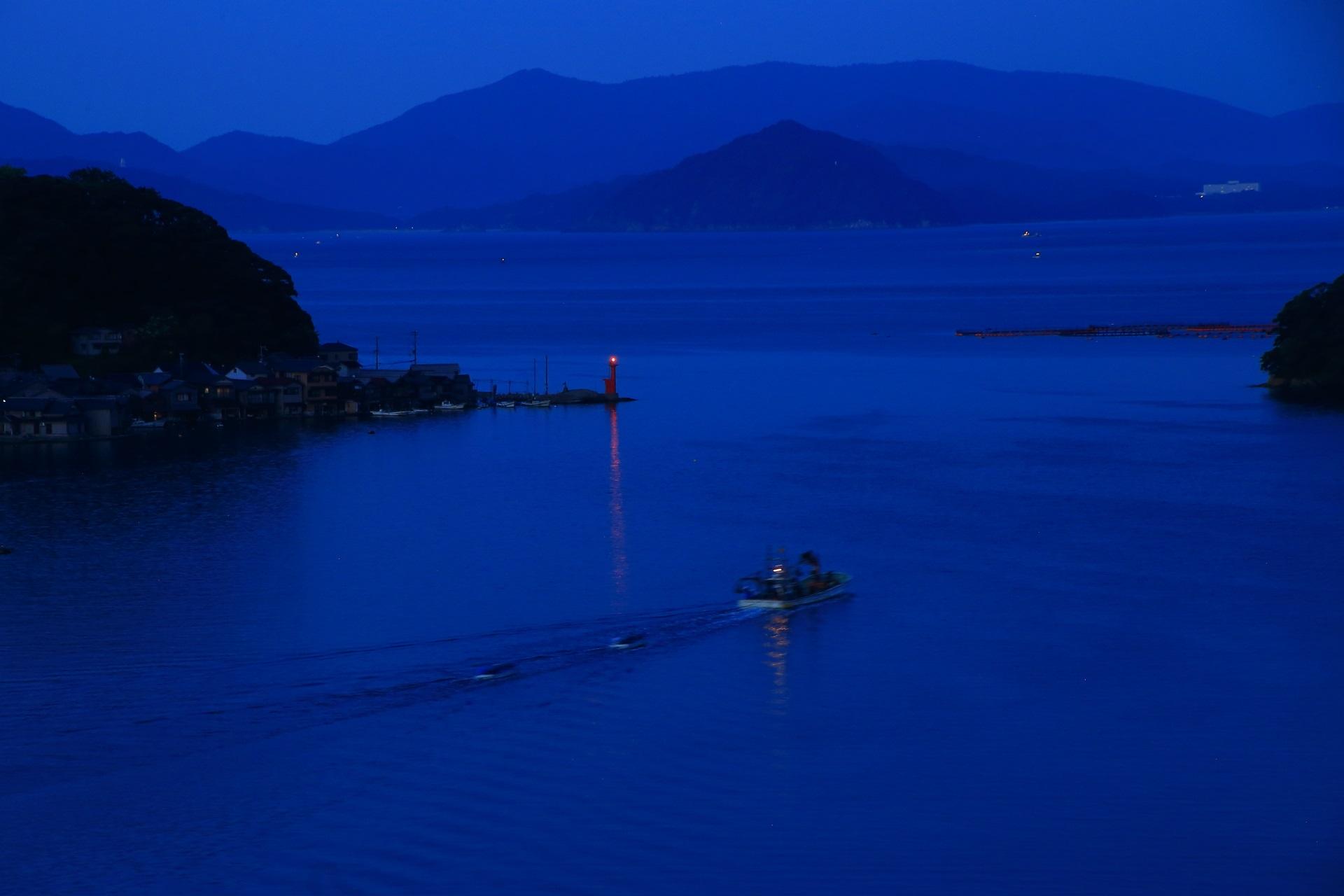 夜明けの海に出港する伊根の漁船