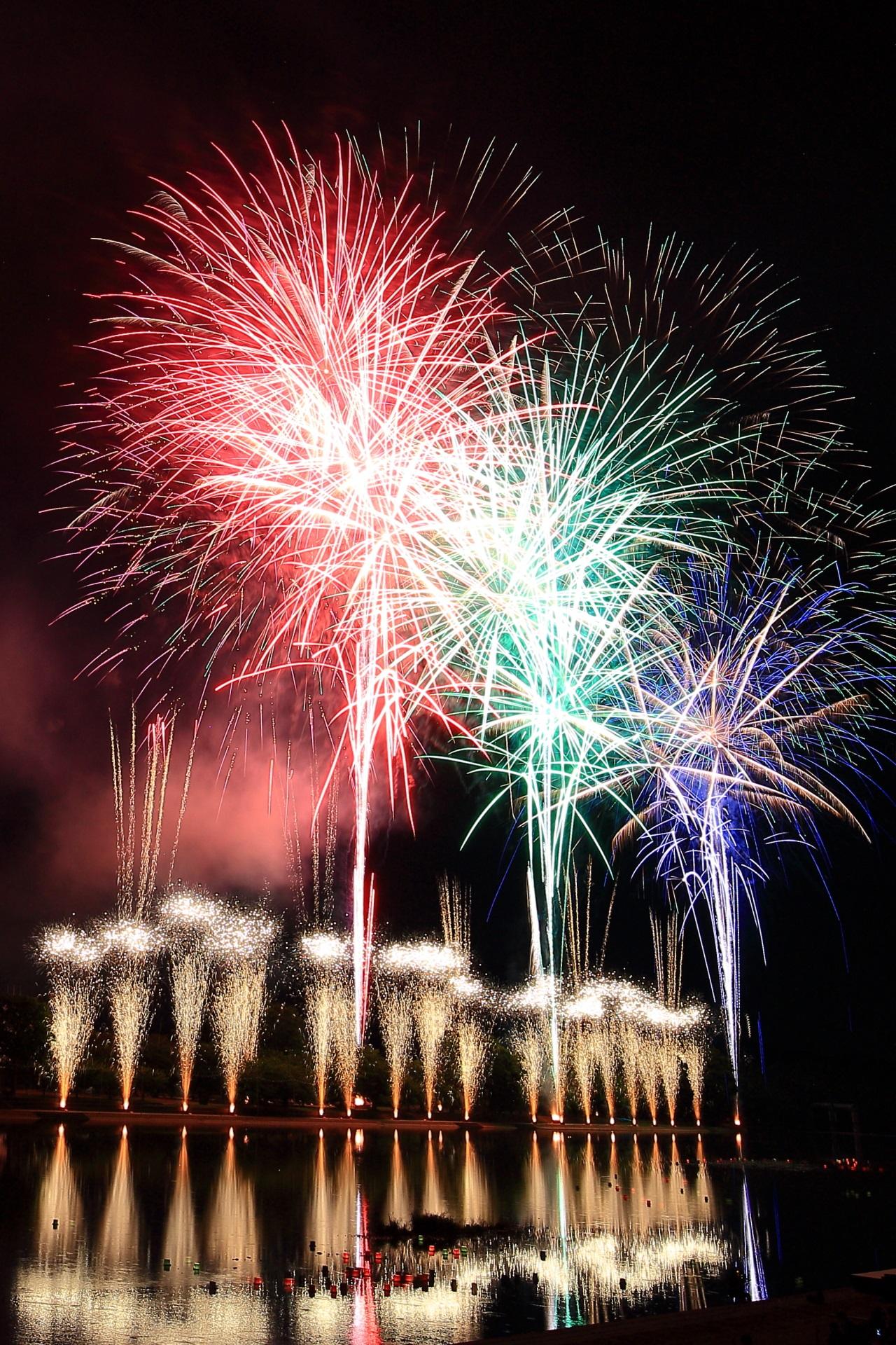 南丹市花火大会の輝く噴水とカラフルな花火