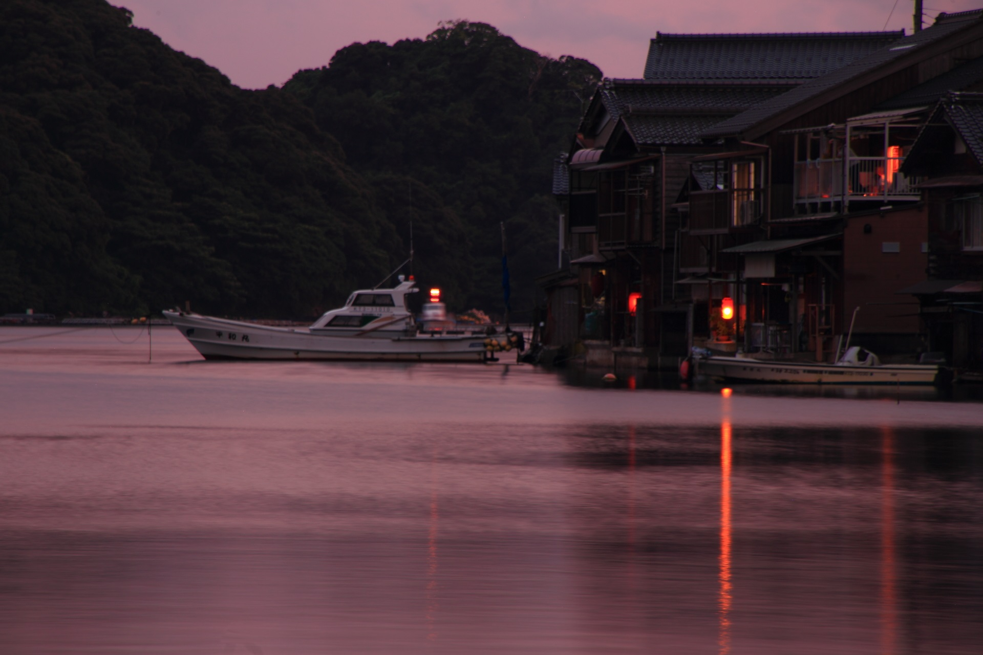 ほんのり赤く夕焼けに染まる漁船