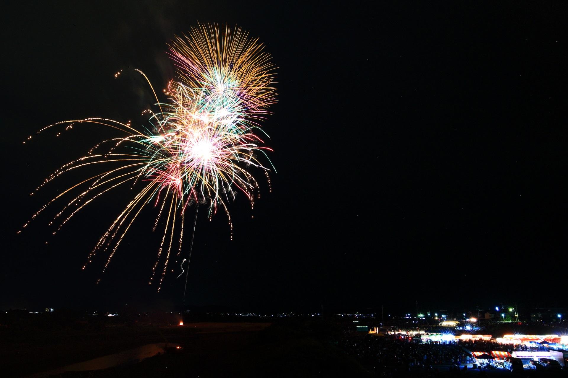 風に流され枝垂れて行く亀岡花火大会の鮮やかな光