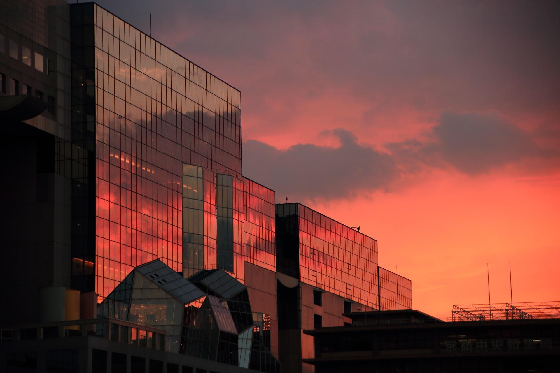 オレンジ色のみならず雲も含めて紫色っぽいところもある駅ビルの夕焼