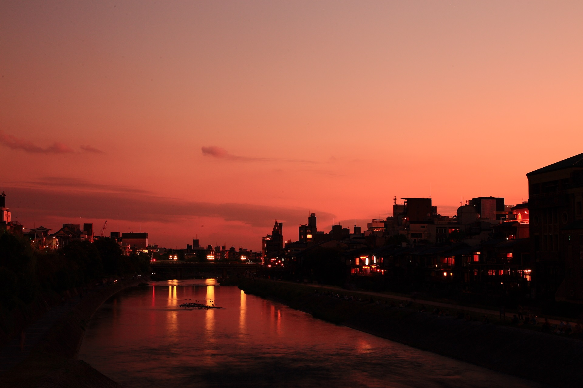 赤い夕焼けに染まる鴨川と街並み