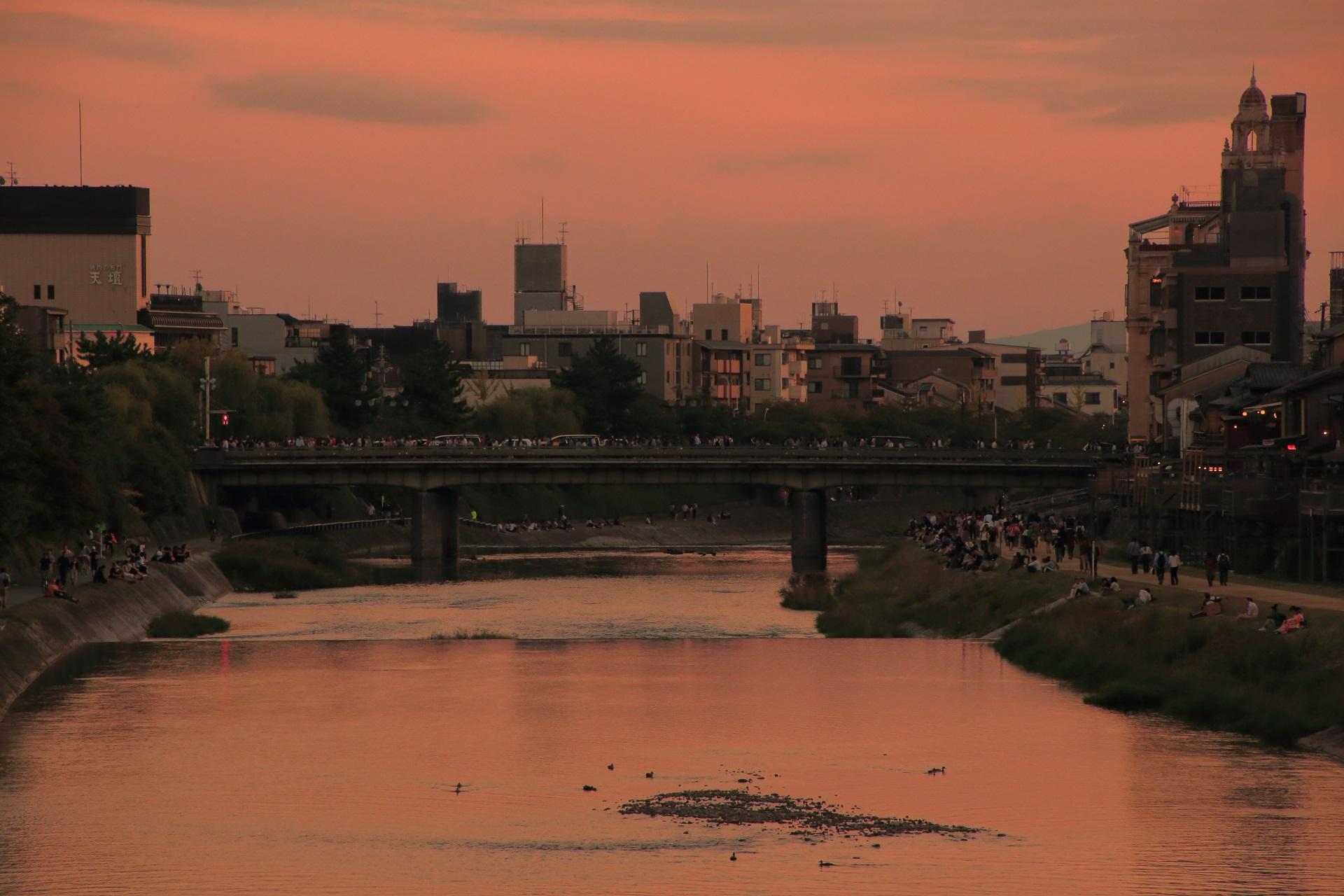 夕焼けに染まる鴨川の四条大橋と東華菜館