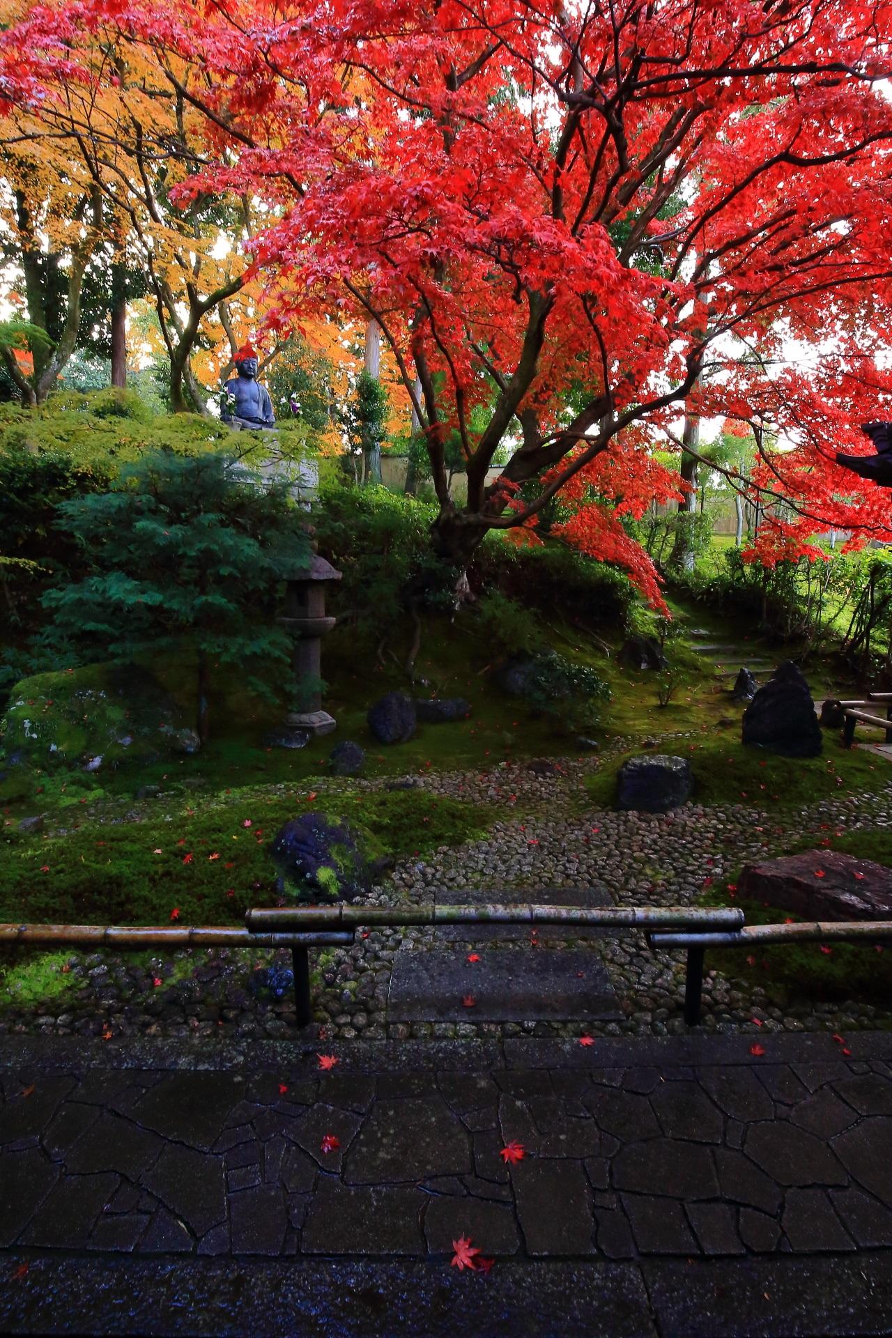 手前の石畳の参道に控えめに散る華やかな紅葉