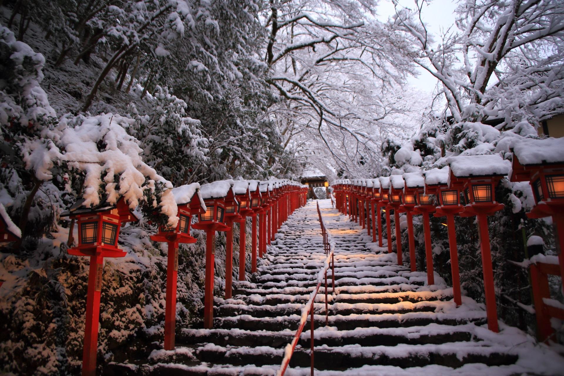 貴船神社の風情ある石段と赤い燈籠の雪景色